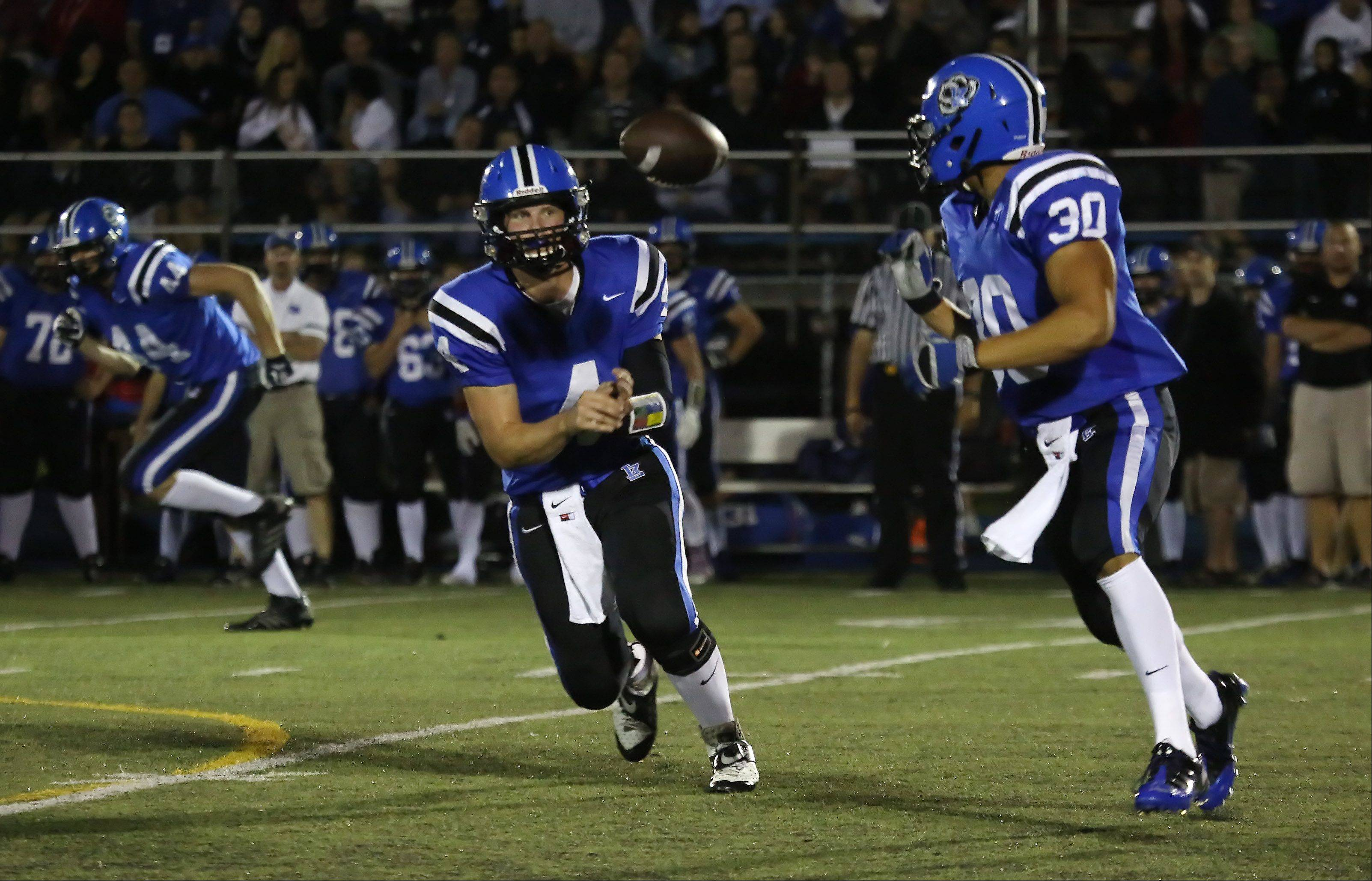 Lake Zurich quarterback Noah Allgood pitches out to running back Ben Klett against Warren on Thursday at Lake Zurich.