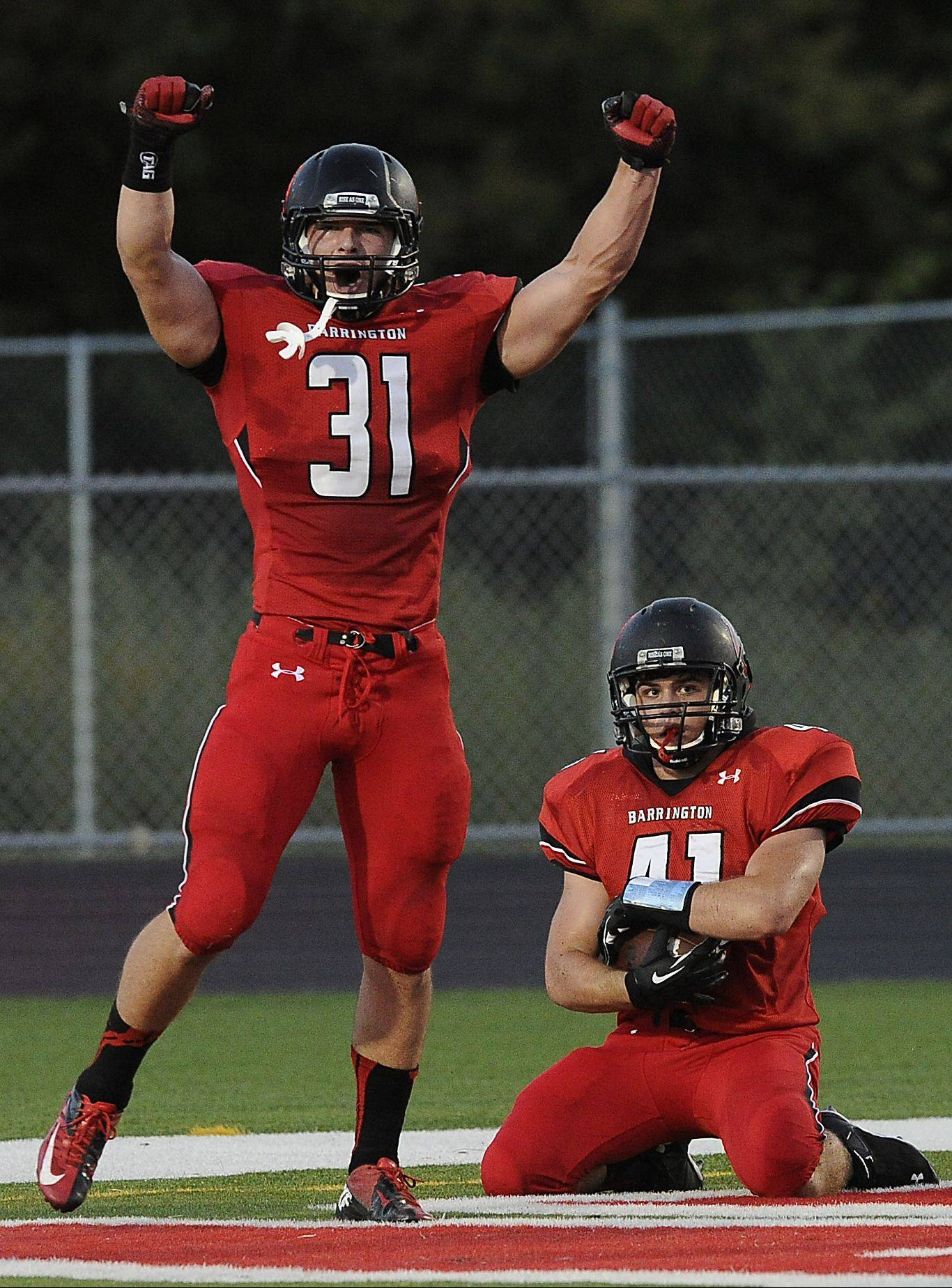 Barrington's Mark Bornhofen recovers a blocked punt for a touchdown as teammate Colin Castagna celebrates during Thursday's matchup against visiting Rolling Meadows.