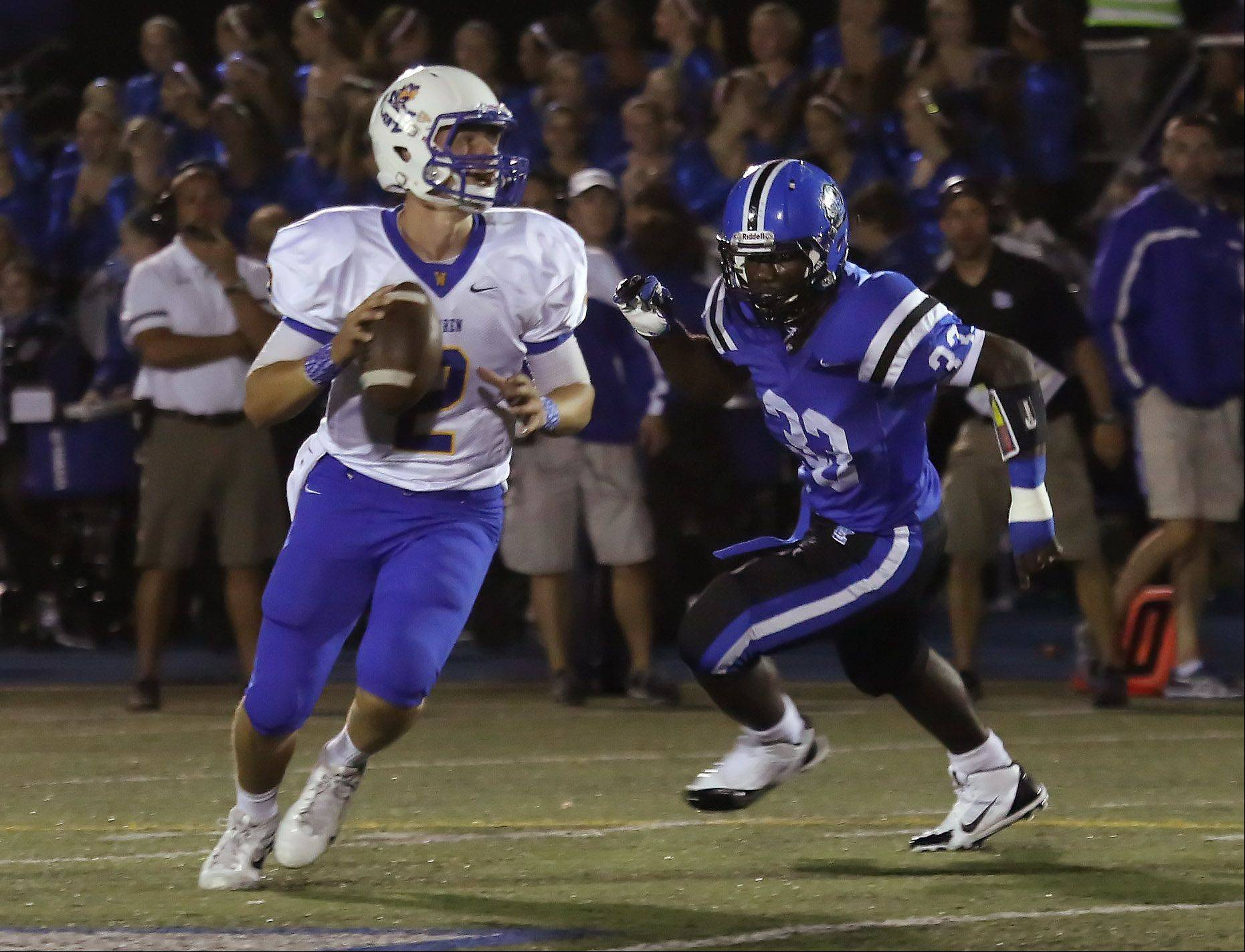 Warren quarterback Andrew Nickell is chased down by Lake Zurich defensive lineman Dominic McNeil .