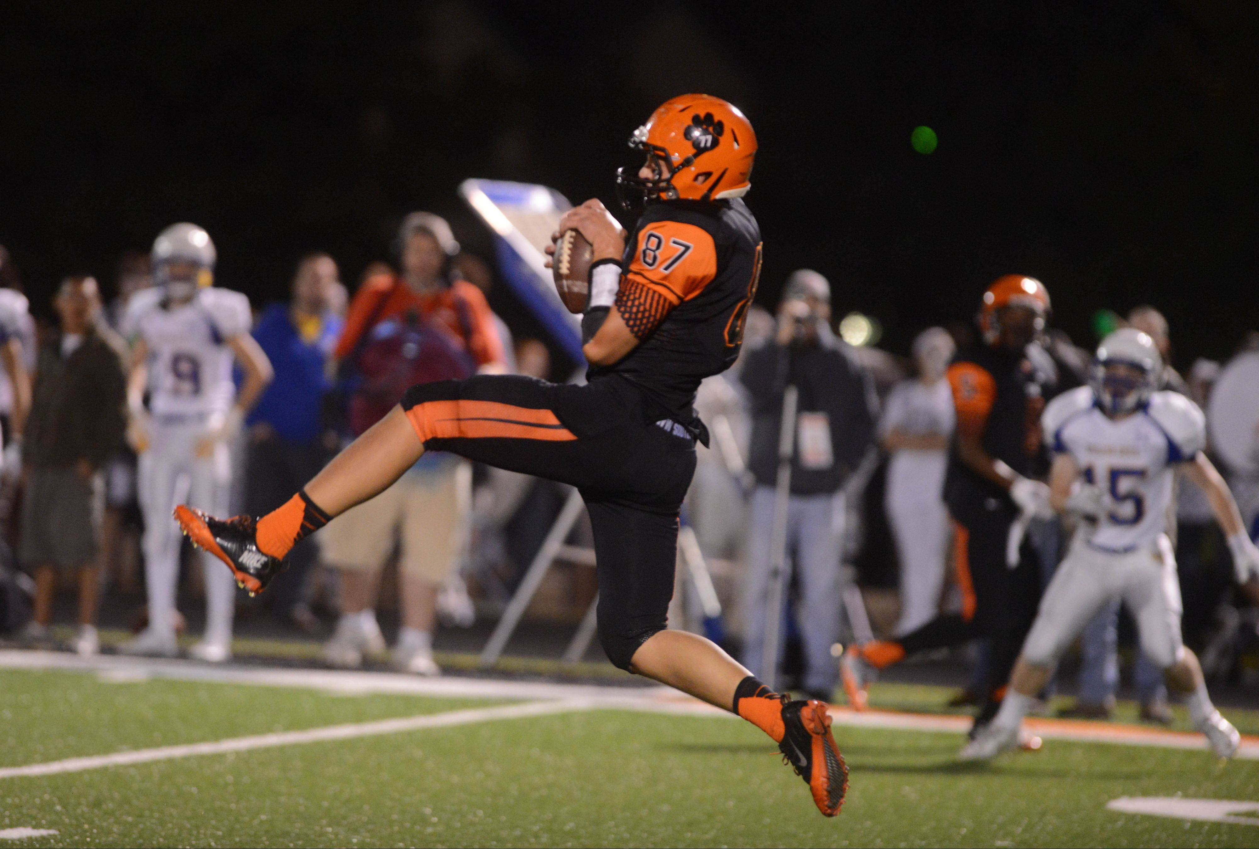 Connor Ostrander of Wheaton Warrenville South pulls down a pass against visiting Wheaton North on Friday.