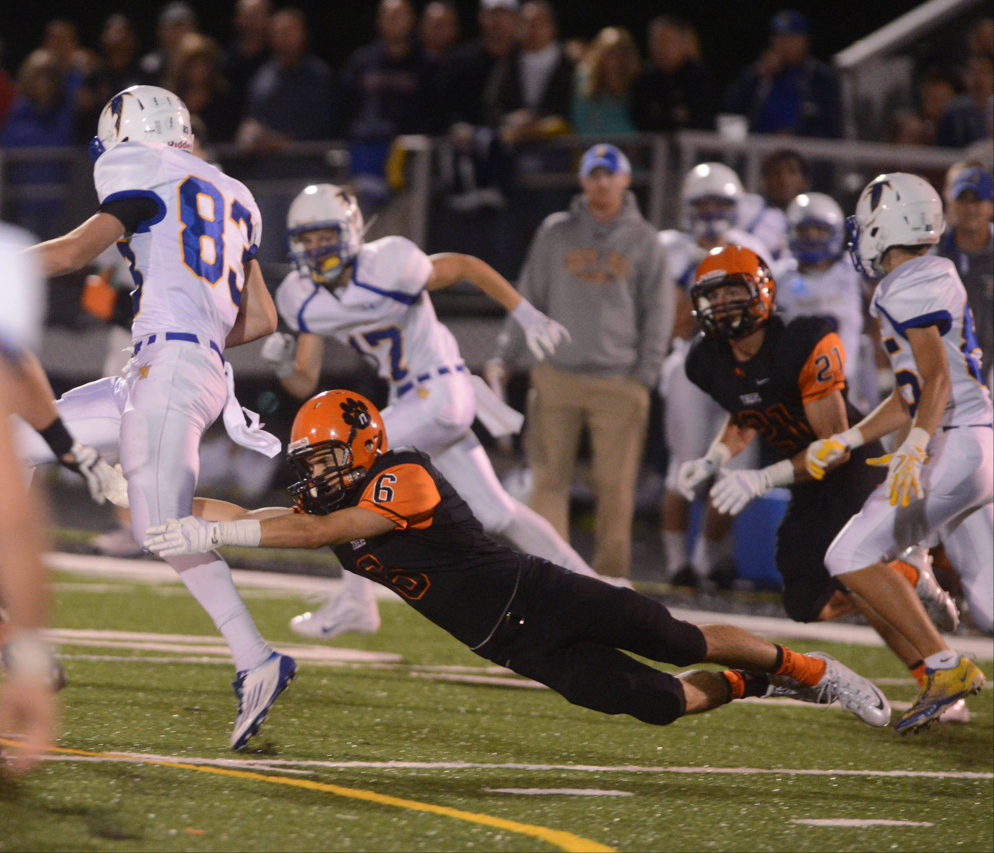 Dan Knight of Wheaton North is pulled down by a diving Mike Cerone of Wheaton Warrenville South on Friday.