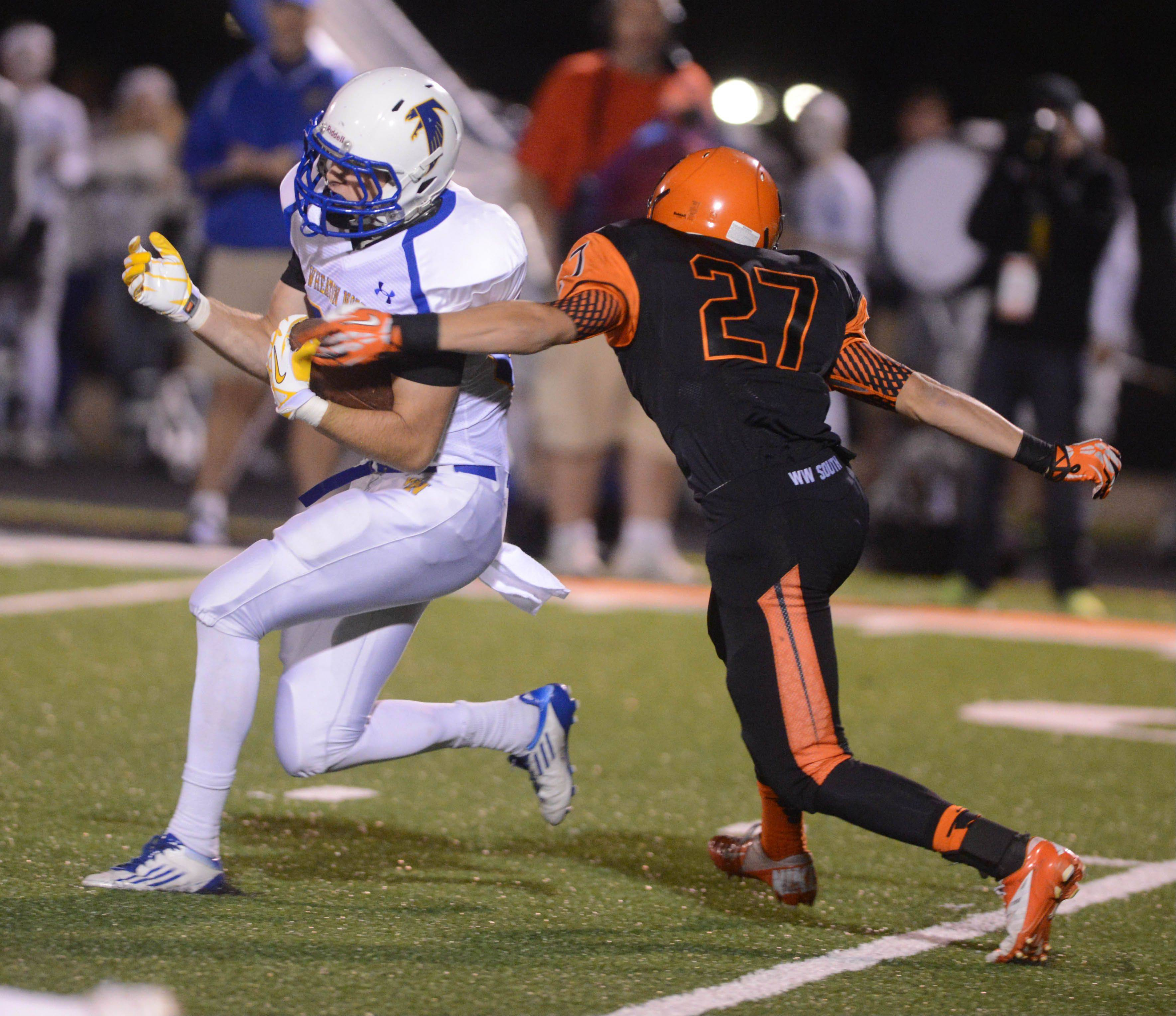 Matt Biegalski of Wheaton North is pulled down by Parker Fuson of Wheaton Warrenville South.