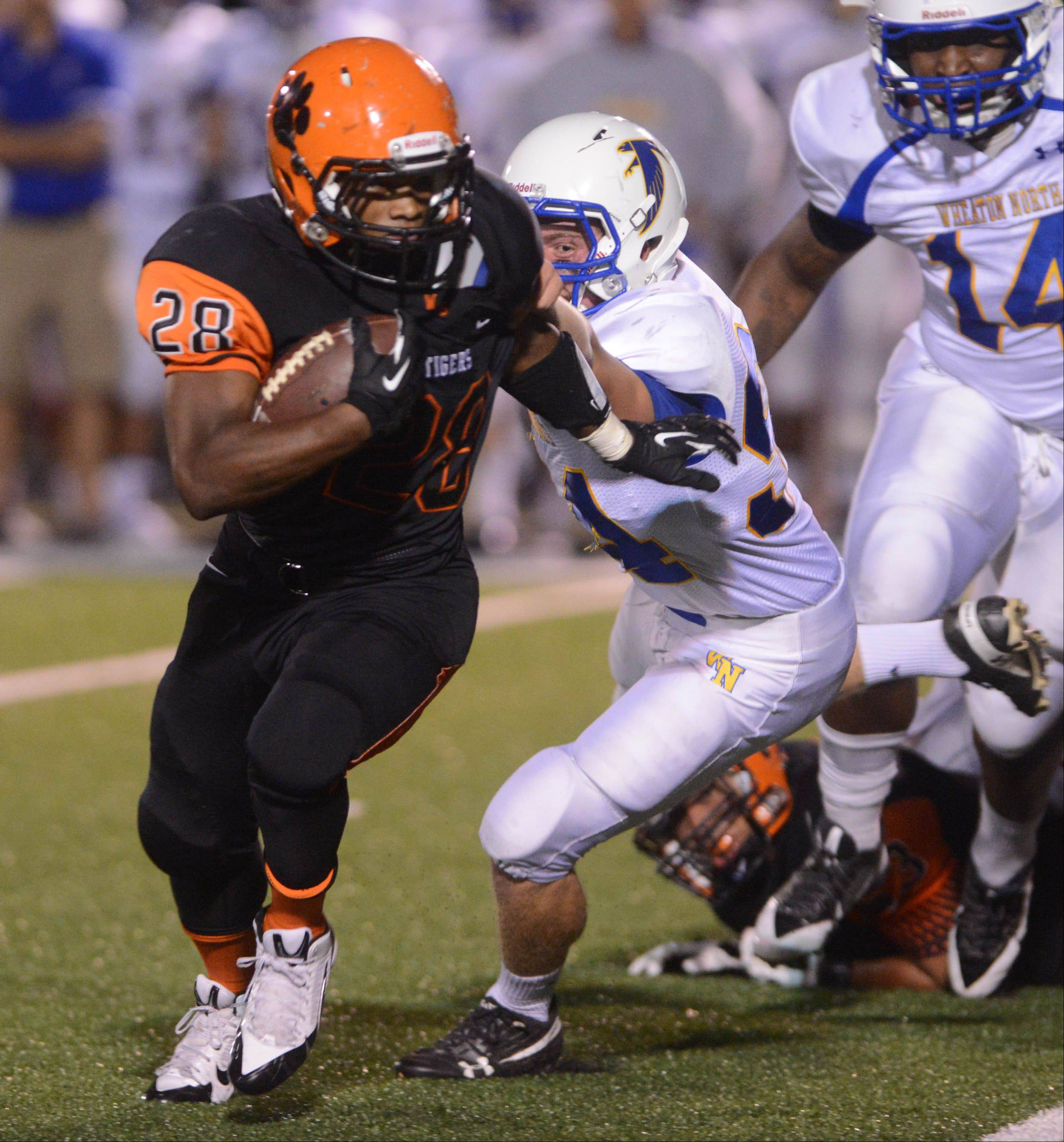 Isaiah Campos of Wheaton Warrenville South out runs a Wheaton North defender during the Wheaton North at Wheaton Warrenville South football game Friday.