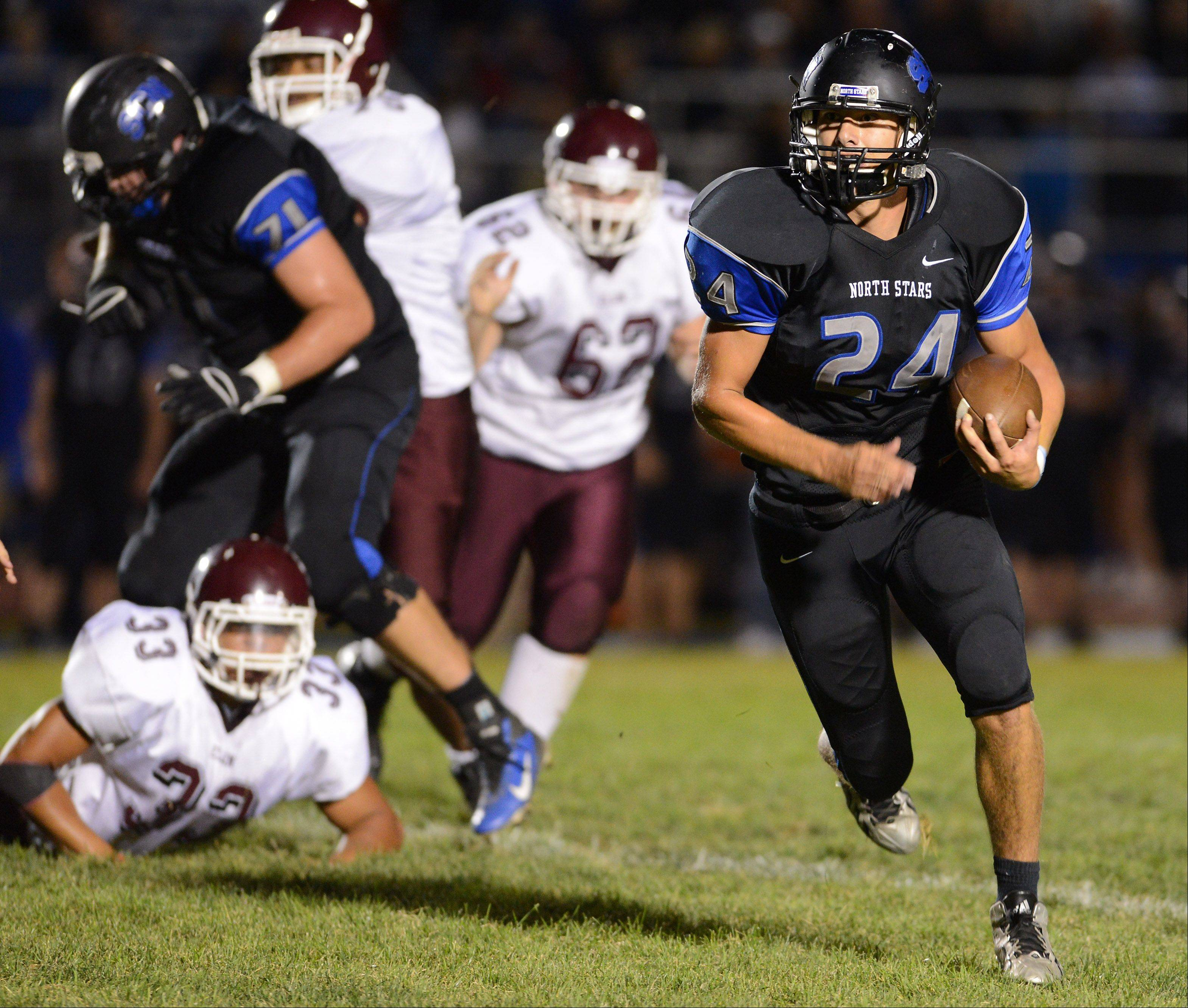 St. Charles North's Evan Kurtz (24) leaves several broken tackles in his wake en route to a big gain against Elgin during Friday's game in St. Charles.