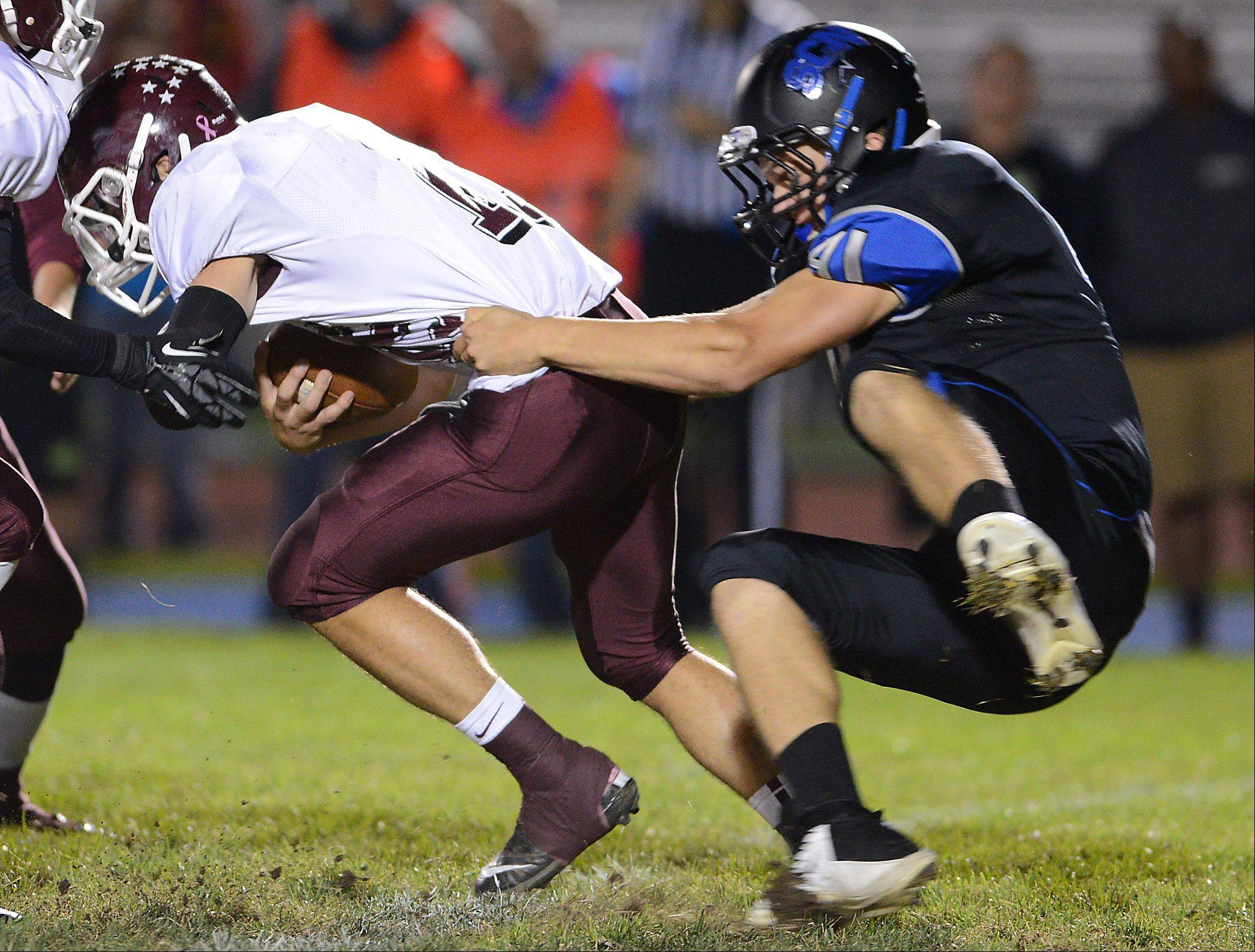 St. Charles North's Jordan Bergren (41) sacks Elgin's Ryan Sitter (15) on the first series of the game during Friday's game in St. Charles.