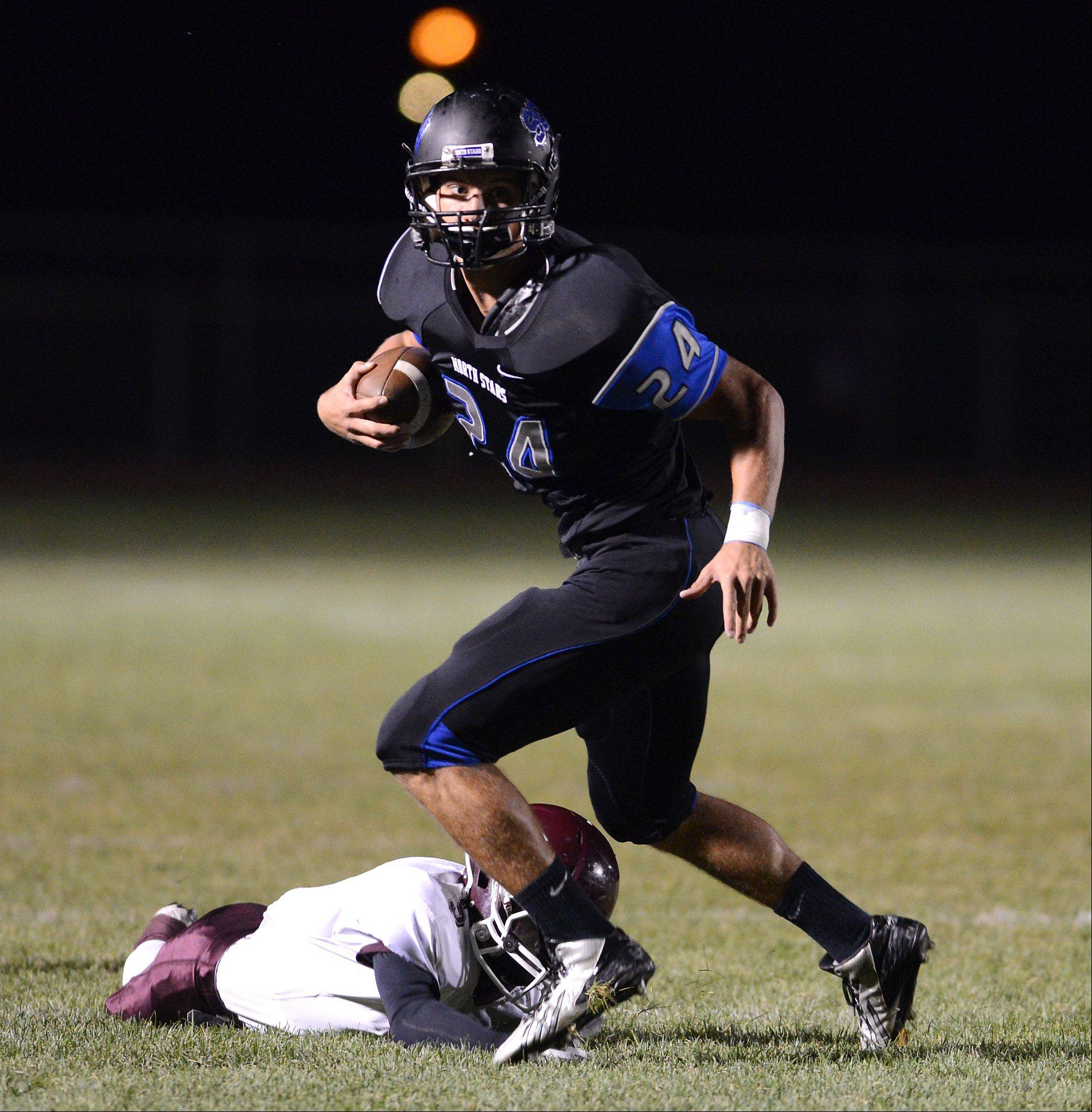 St. Charles North's Evan Kurtz heads upfield for a long gain after breaking a tackle attempt by Elgin's Clay White .