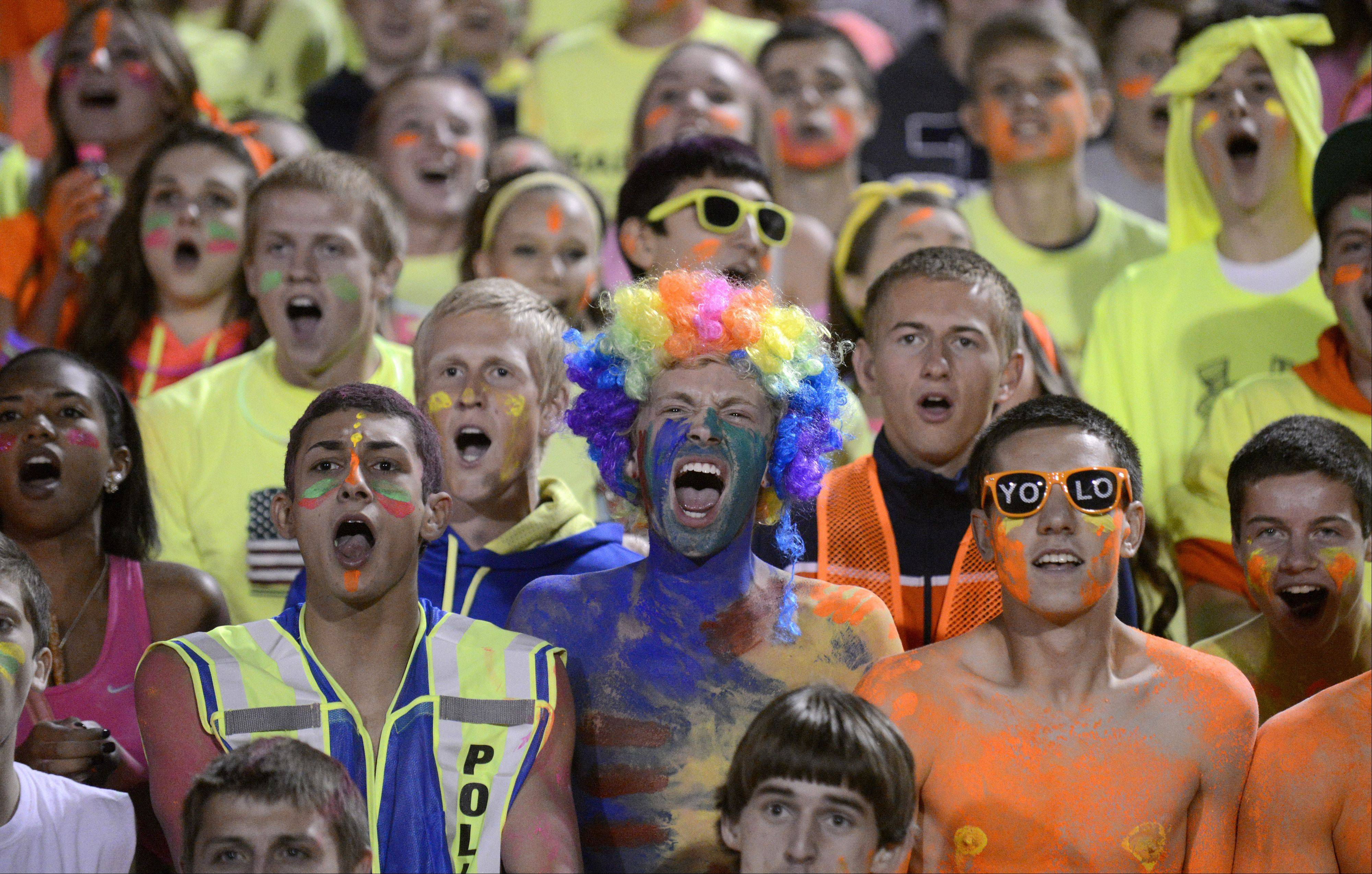 Cary-Grove fans Anthony Abbate, Charlie Price, and Kevin Cooke scream during the kick-off.