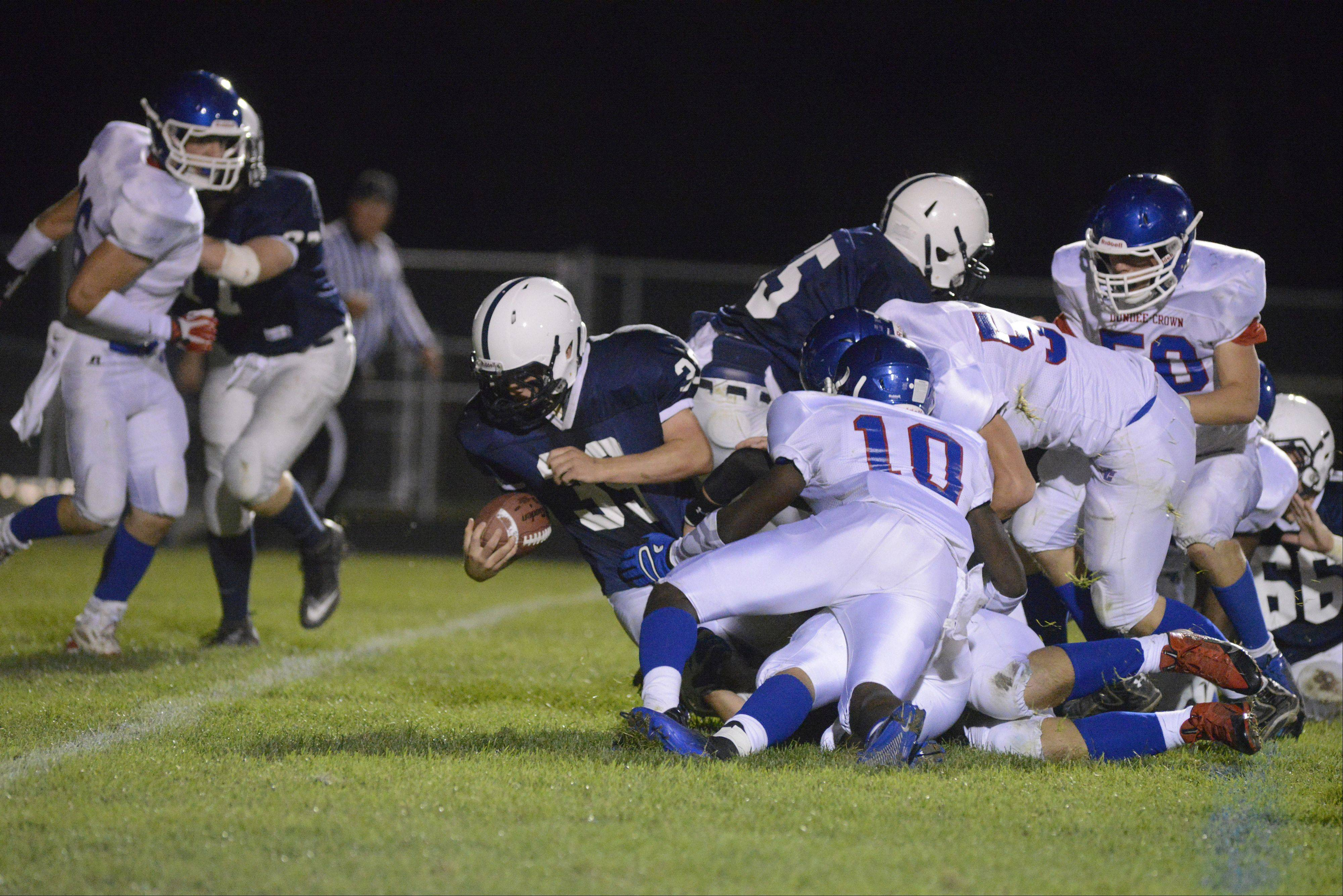 Cary-Grove's Tyler Pennington pops out of a pile up of Trojans and Chargers reaching for the goal line in the first quarter.