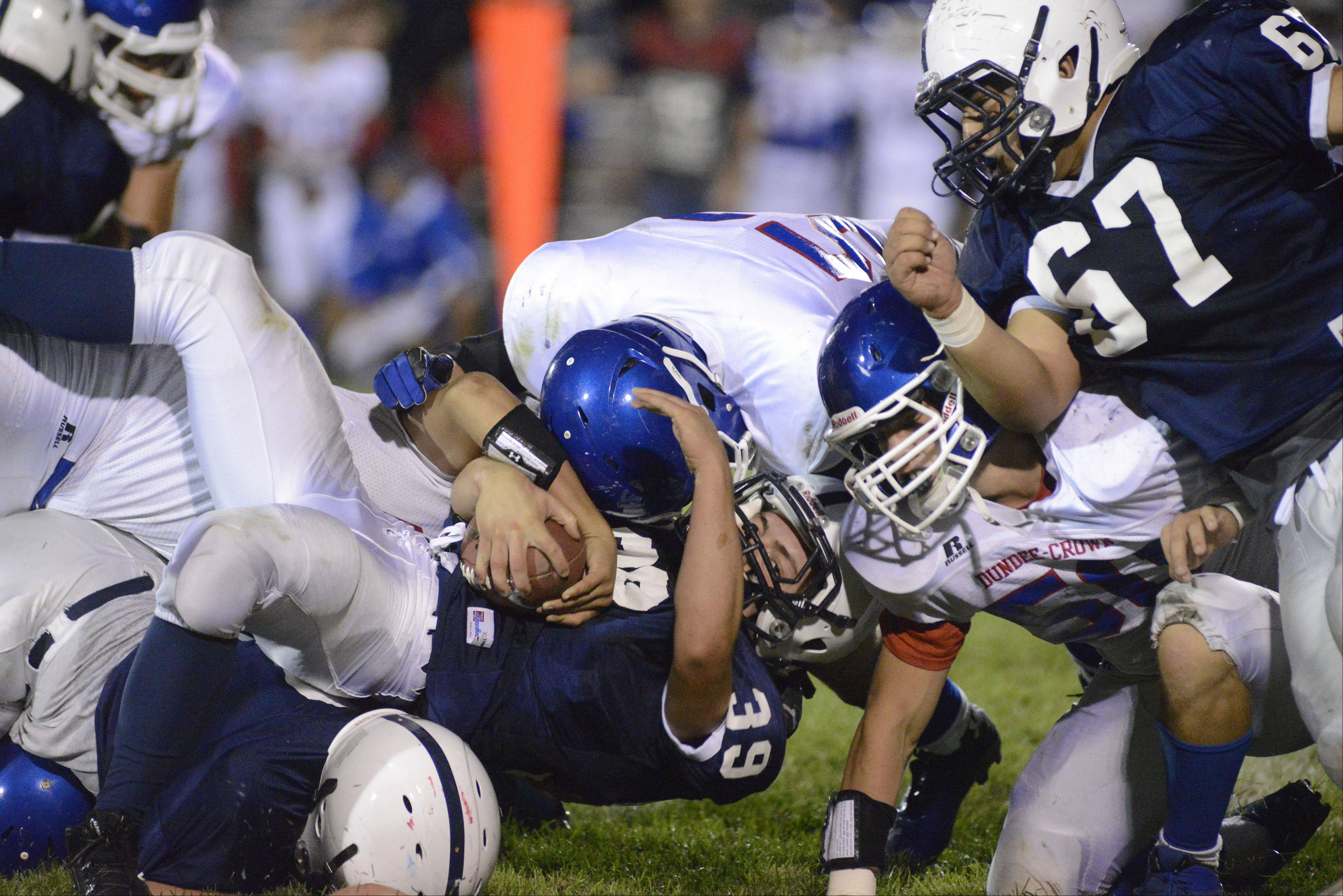 Cary-Grove's Tyler Pennington is taken down by Dundee-Crown's Xzavier Torres and Zach Thelen in the second quarter.