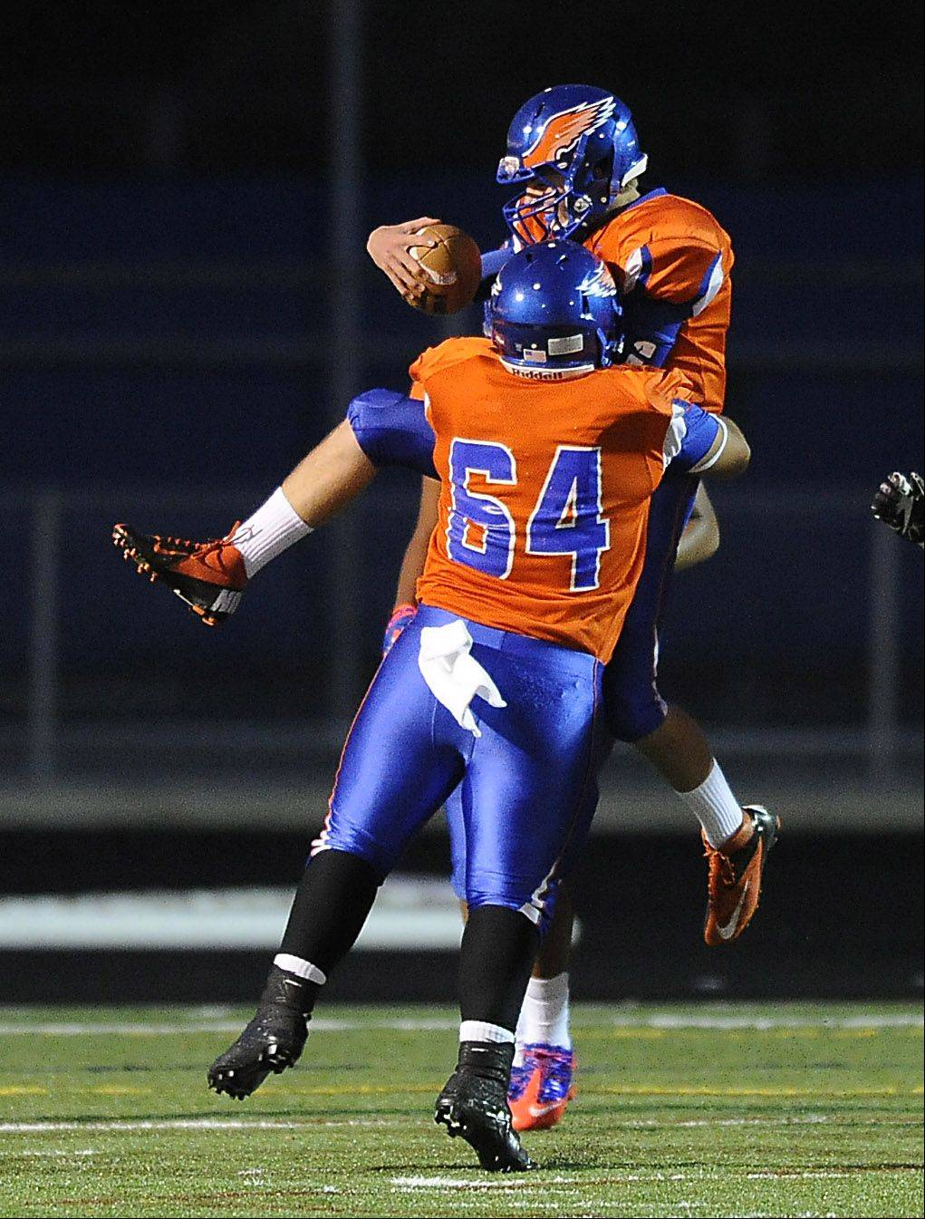 Hoffman Estates' Jeffery Mayes jumps into the arms of his teammate Baldemar Camacho after running a 77-yard touchdown run in the first quarter.