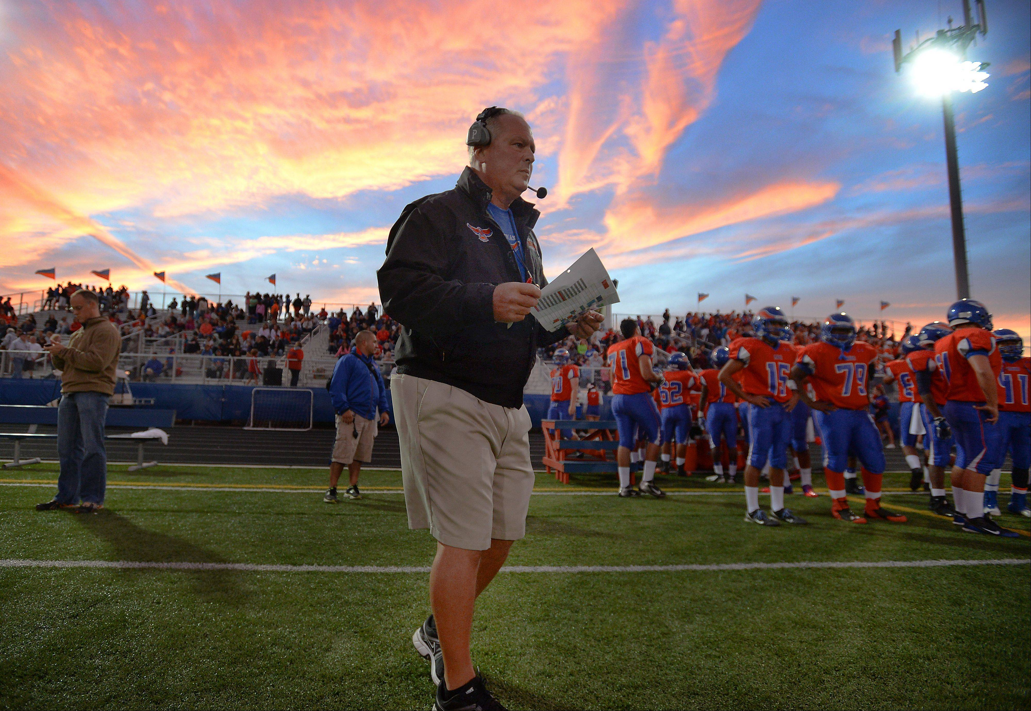 Hoffman Estates' coach Mike Donatucci looks over the game plan .