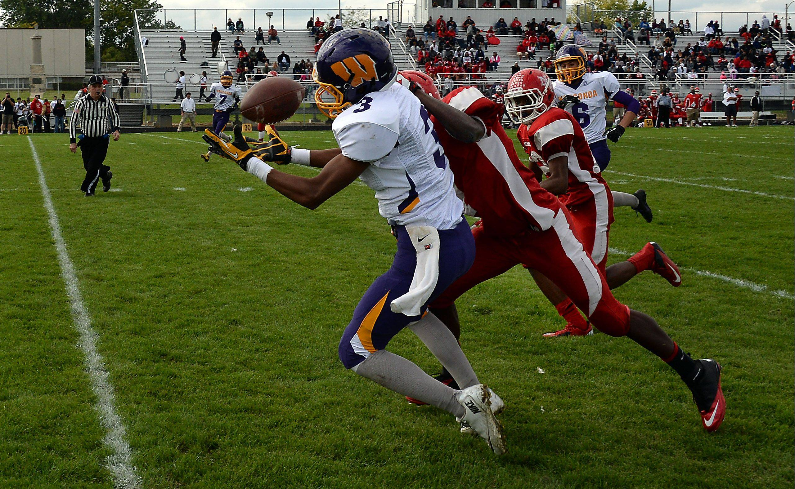 Wauconda's Josh Anderson hauls in a pass play despite pressure from North Chicago's Brandon Coofer in the second quarter for major yardage at North Chicago on Saturday.