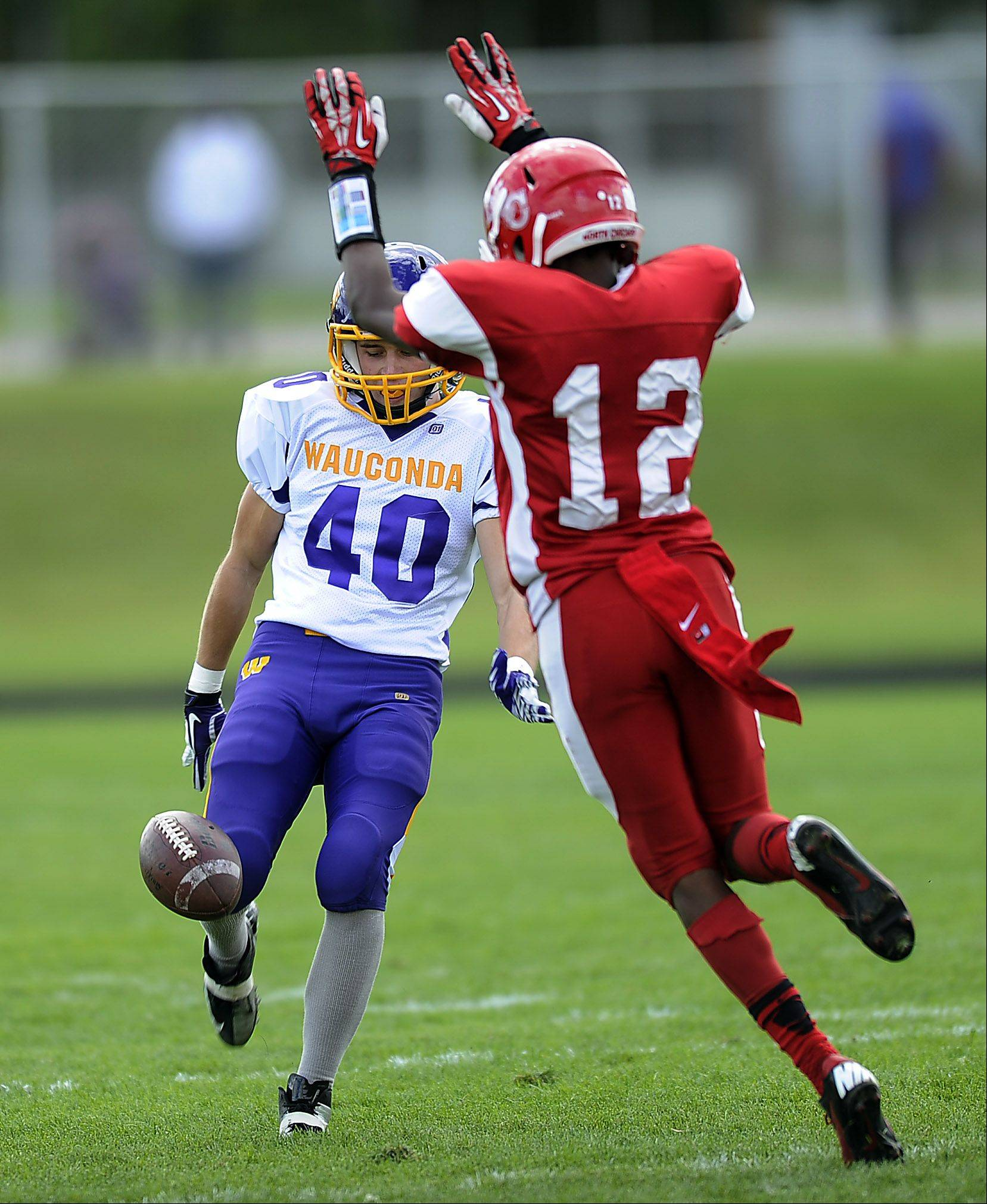 Wauconda's Elliot Hill has his punt blocked by North Chicago's Donte Rowell in the first quarter of varsity footbll at North Chicago High School on Saturday.