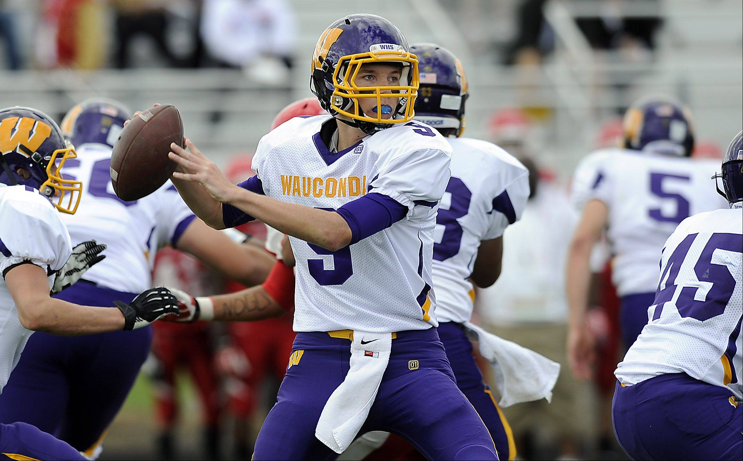 Wauconda's Kevin Malisheski looks for a receiver downfield and fires to Josh Anderson in the first half of varsity footbll at North Chicago High School on Saturday.