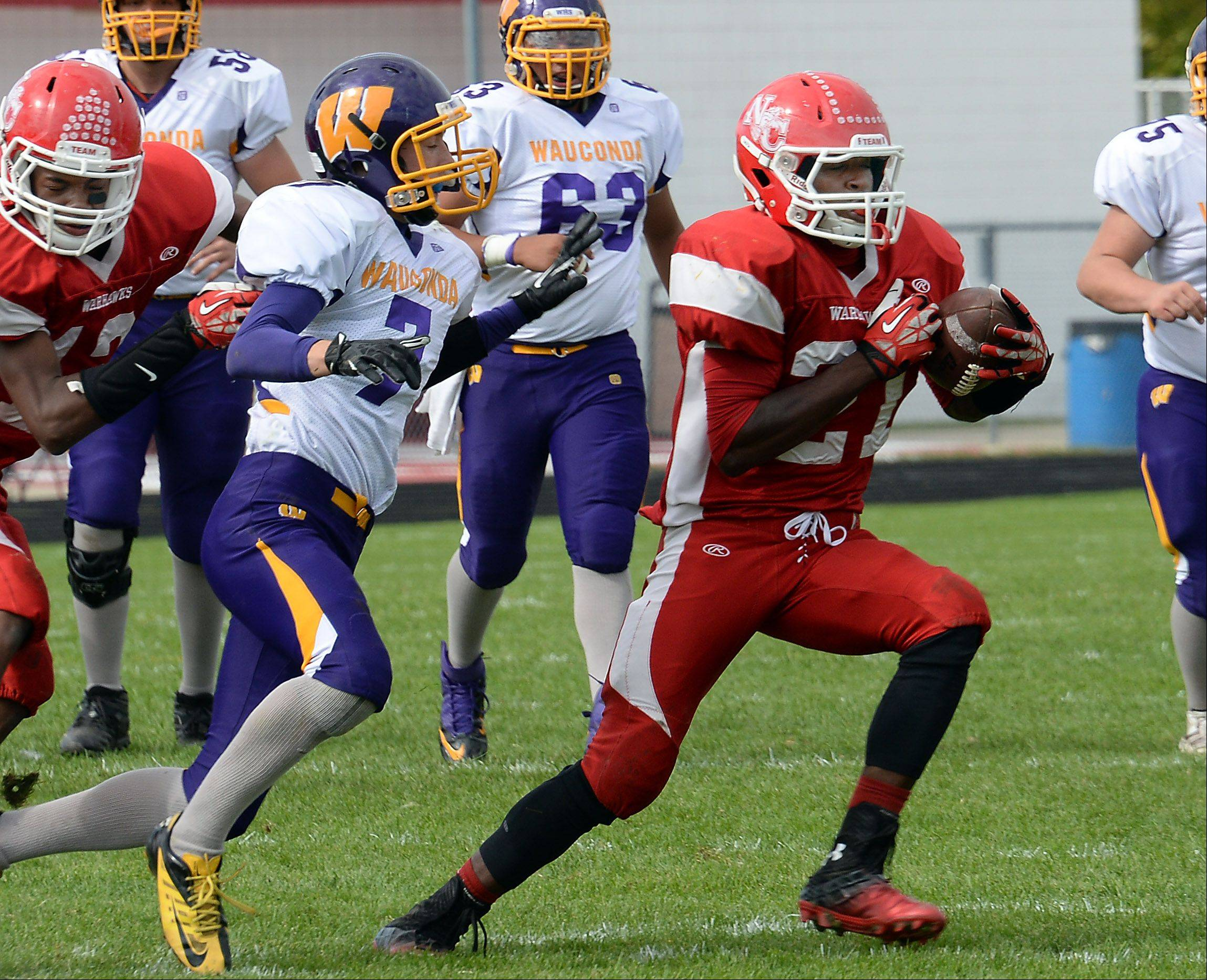 Wauconda's Joey Pausa is the intended receiver but North Chicago's Tazari Bryant picks it off for the interception in the first half of varsity footbll at North Chicago High School on Saturday.
