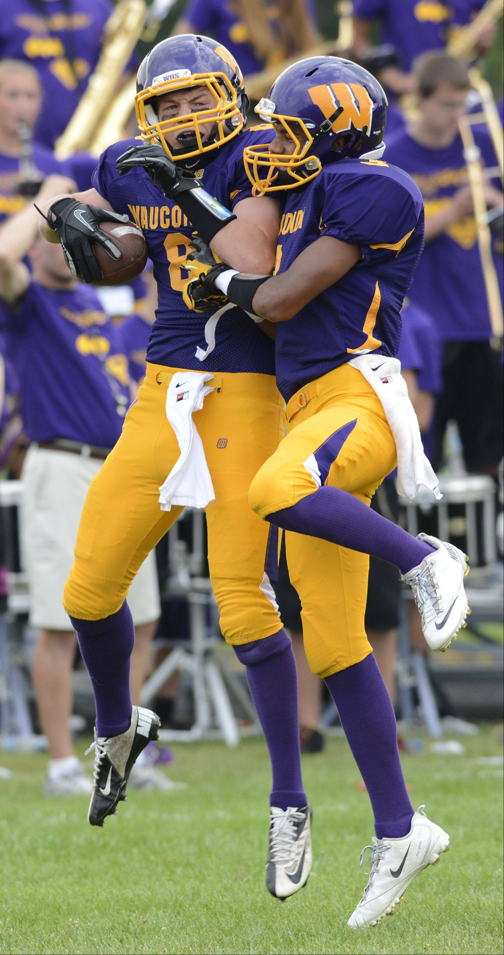 Wauconda's Alex Schwickrath, left, celebrates a first-quarter touchdown with teammate Josh Anderson during Saturday's game.