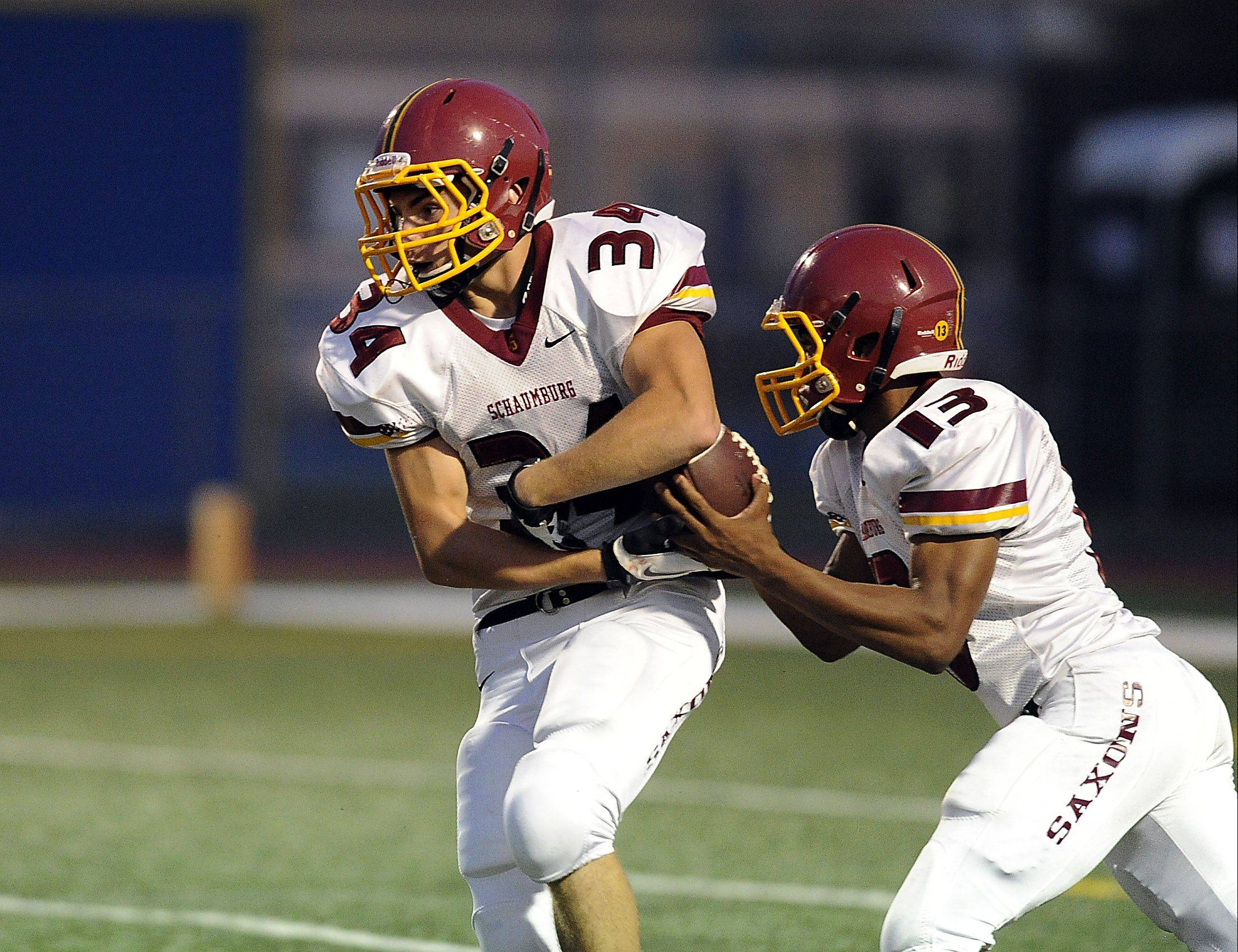 Schaumburg quarterback Stacey Smith fakes a handoff to Michael Jones before going for a score against Wheeling in Week 2. The Saxons host another MSL unbeaten, Barrington, on Friday.