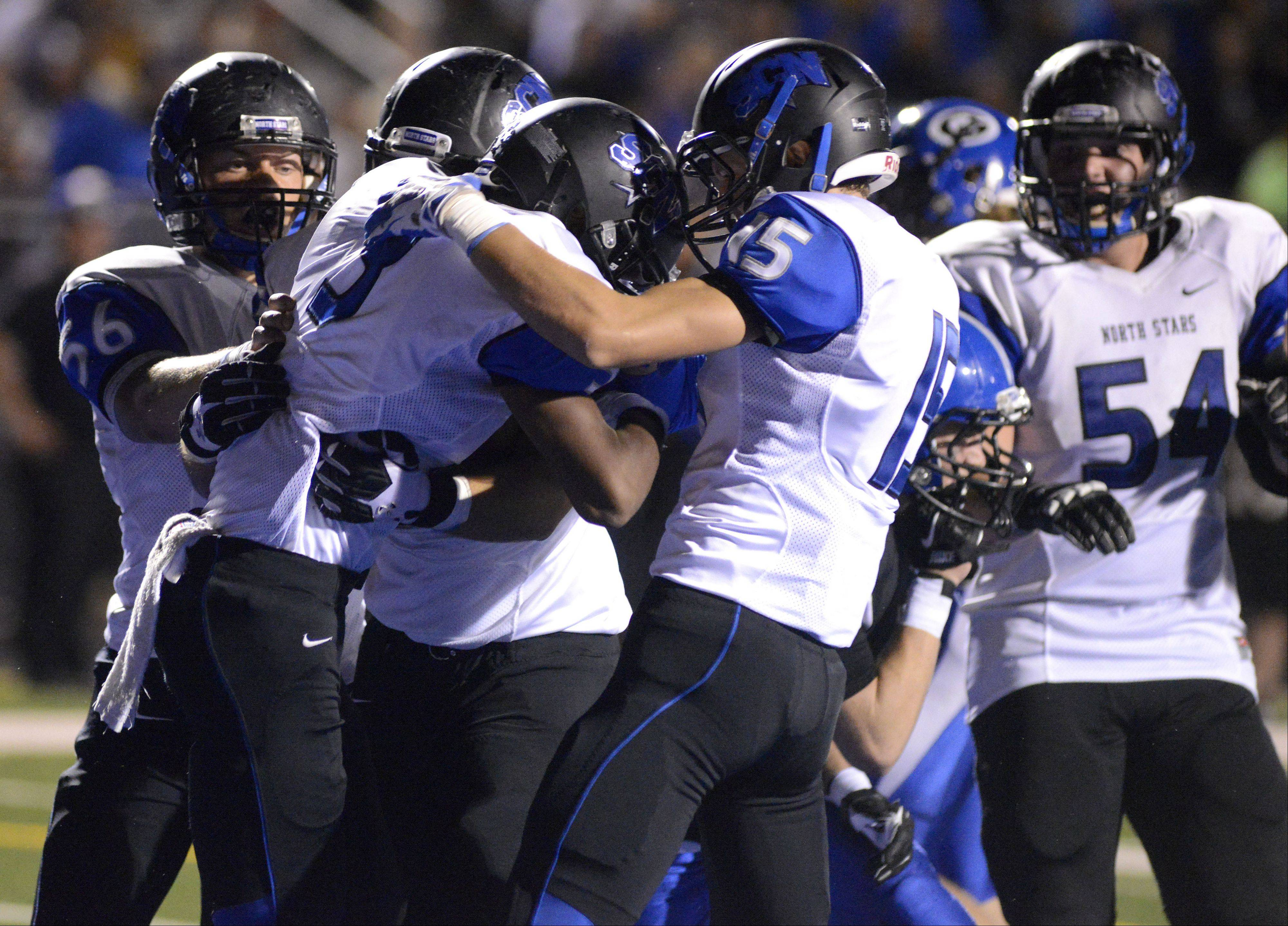 St. Charles North's Jon Merriwether is congratulated by teammates after scoring a touchdown at the start of the third quarter.