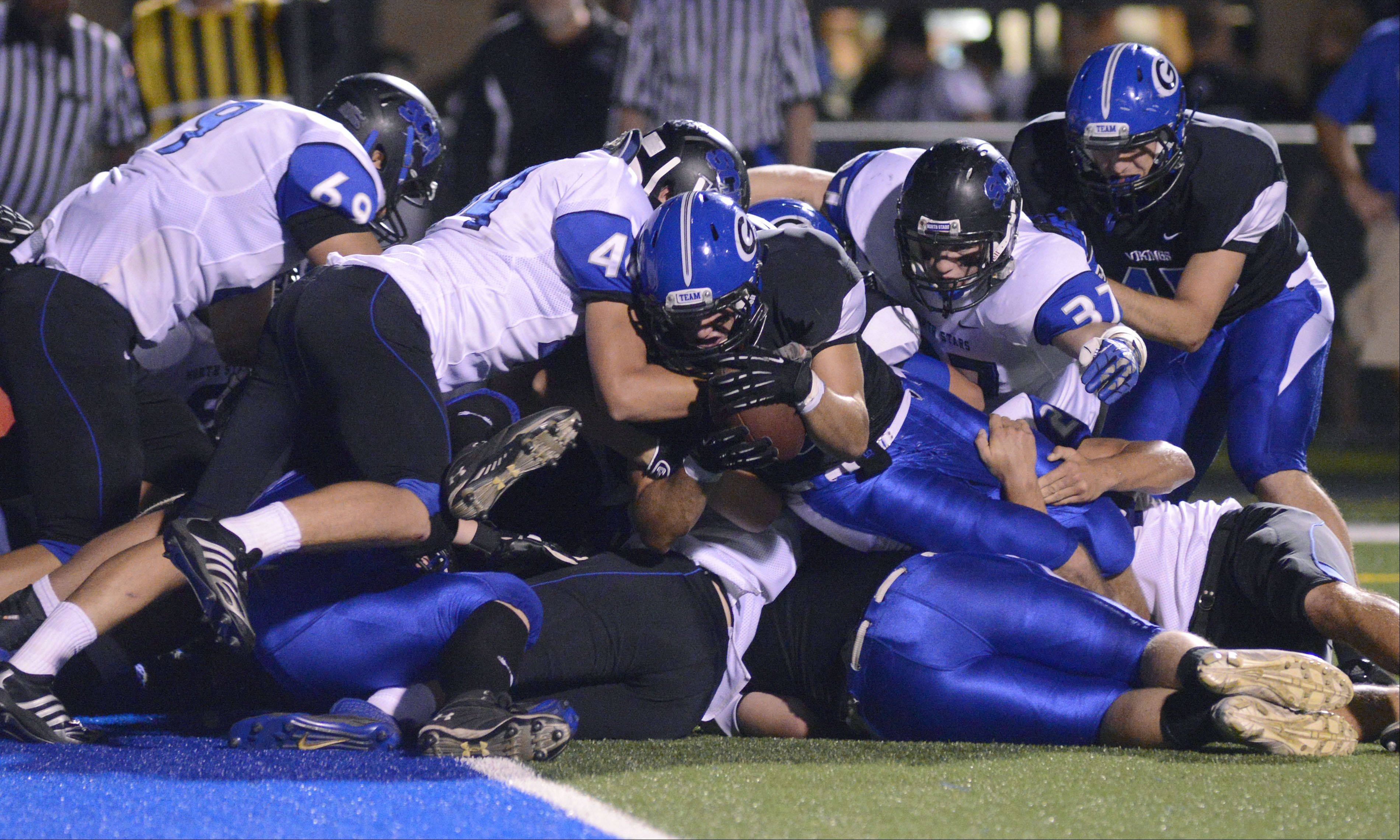 Ball carrier Geneva's T.J. Miller is stopped cold and piled upon just inches from the end zone in the first quarter.