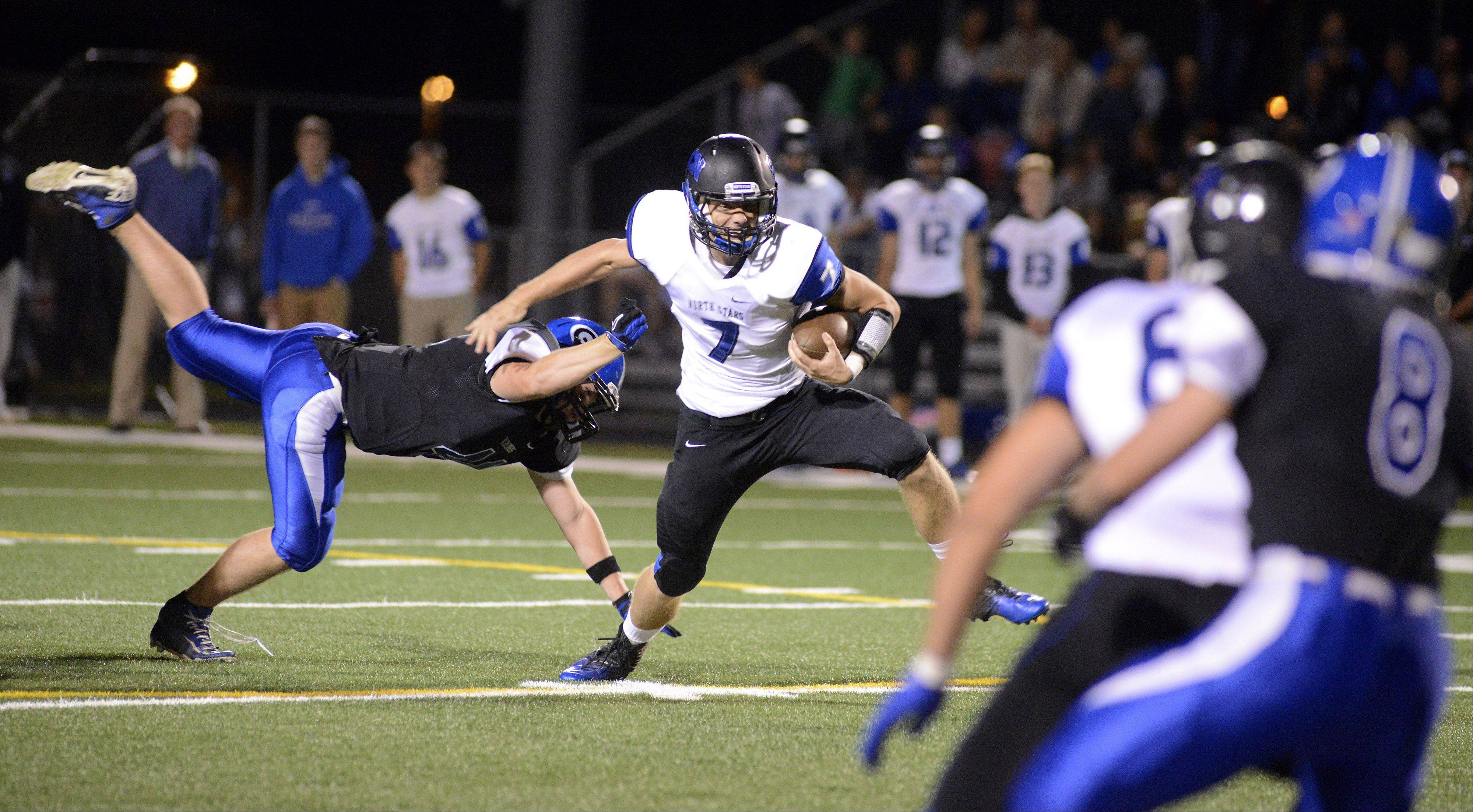St. Charles North quarterback Erik Mille shakes off Geneva's Wyatt Shodeen in the first quarter.