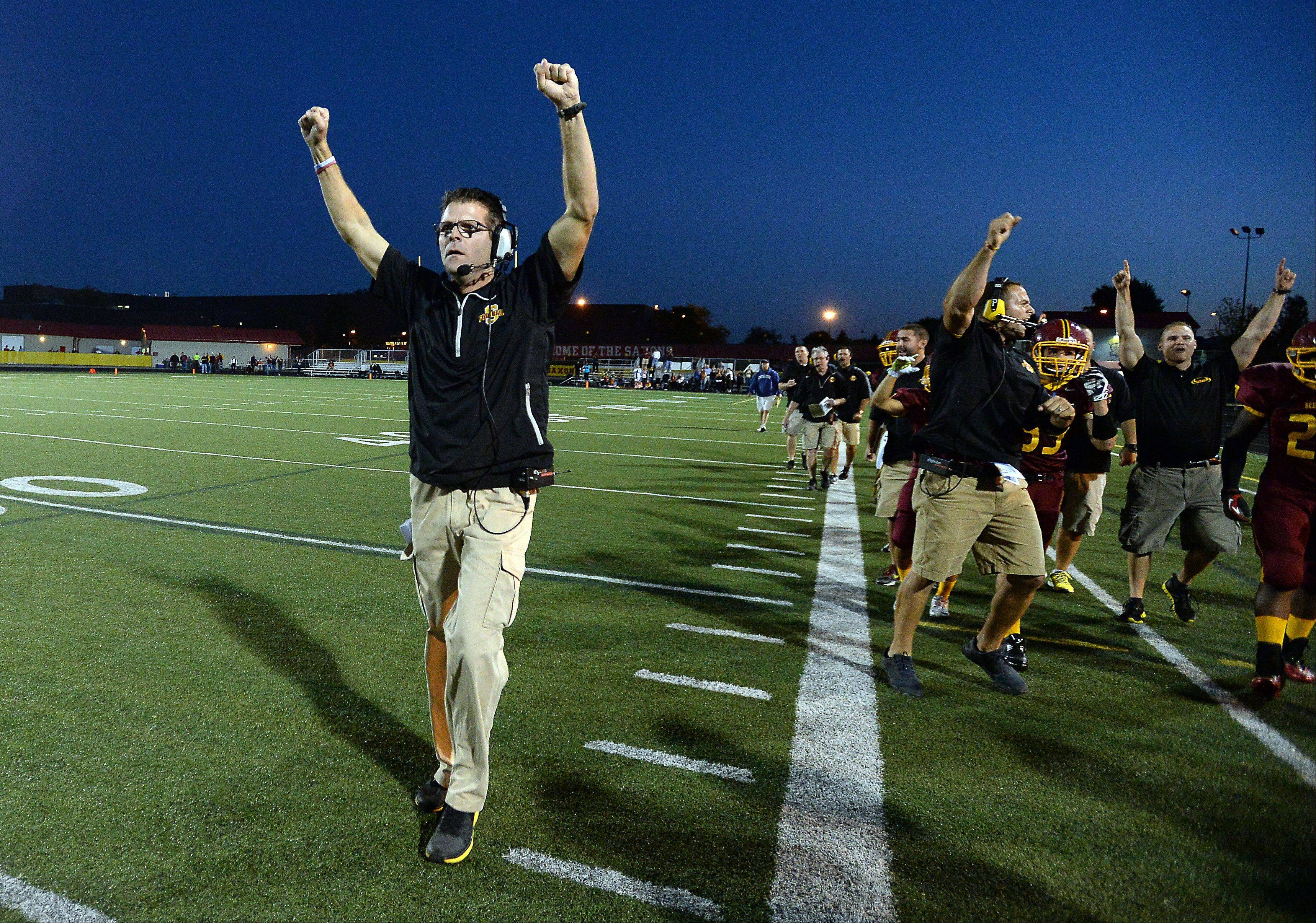 Schaumburg's head coach Mark Stilling celebrates a Luke Gruszka 62-yard touchdown run in the first quarter.