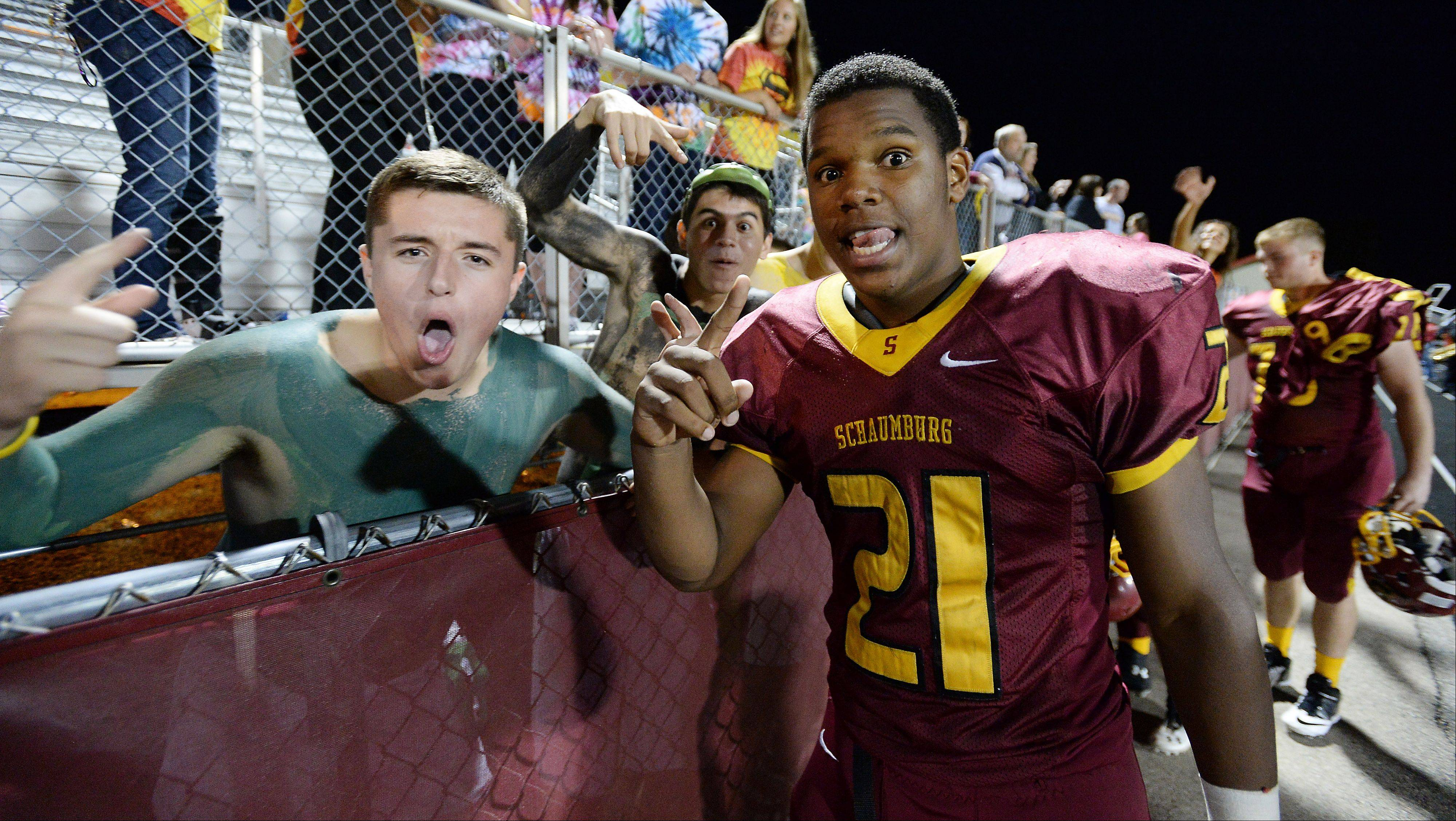 Schaumburg's Justice Macneal-Young celebrates with the fans after the Saxons beat Barrington 33-21.