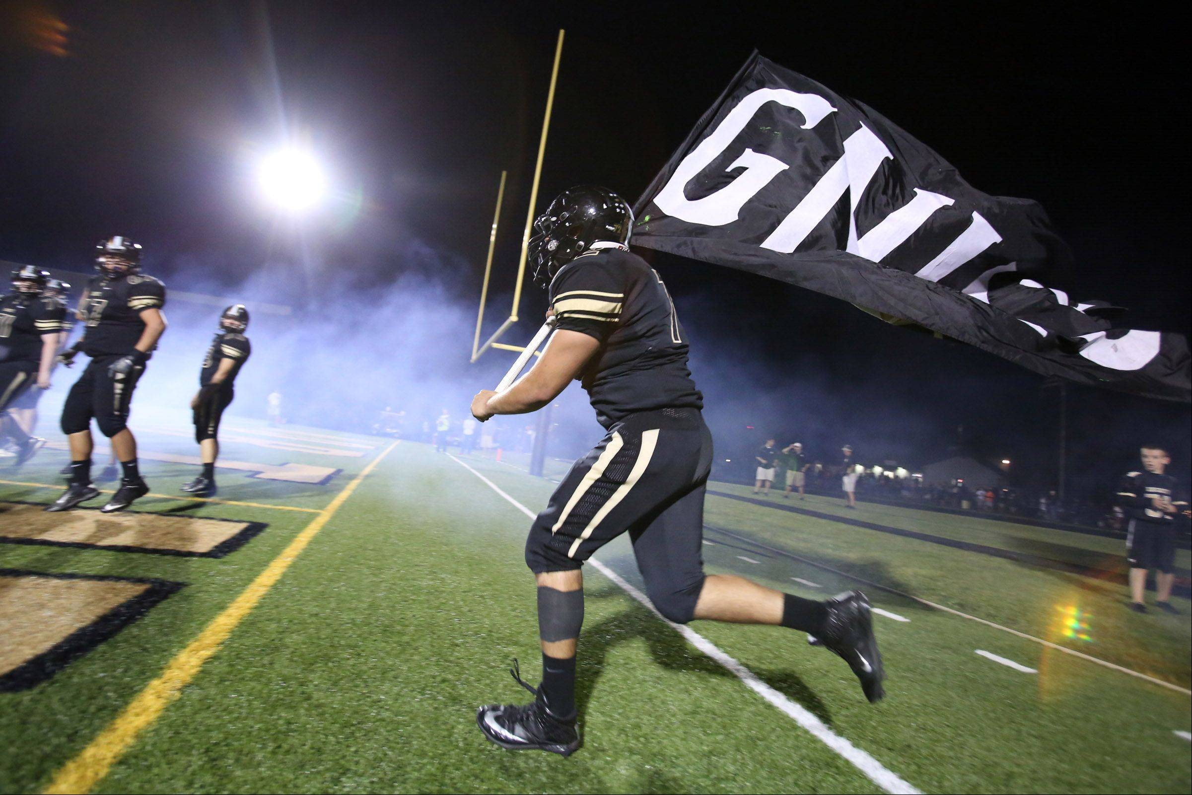 Grayslake North defensive lineman Noe Perez runs the team flag on the field.