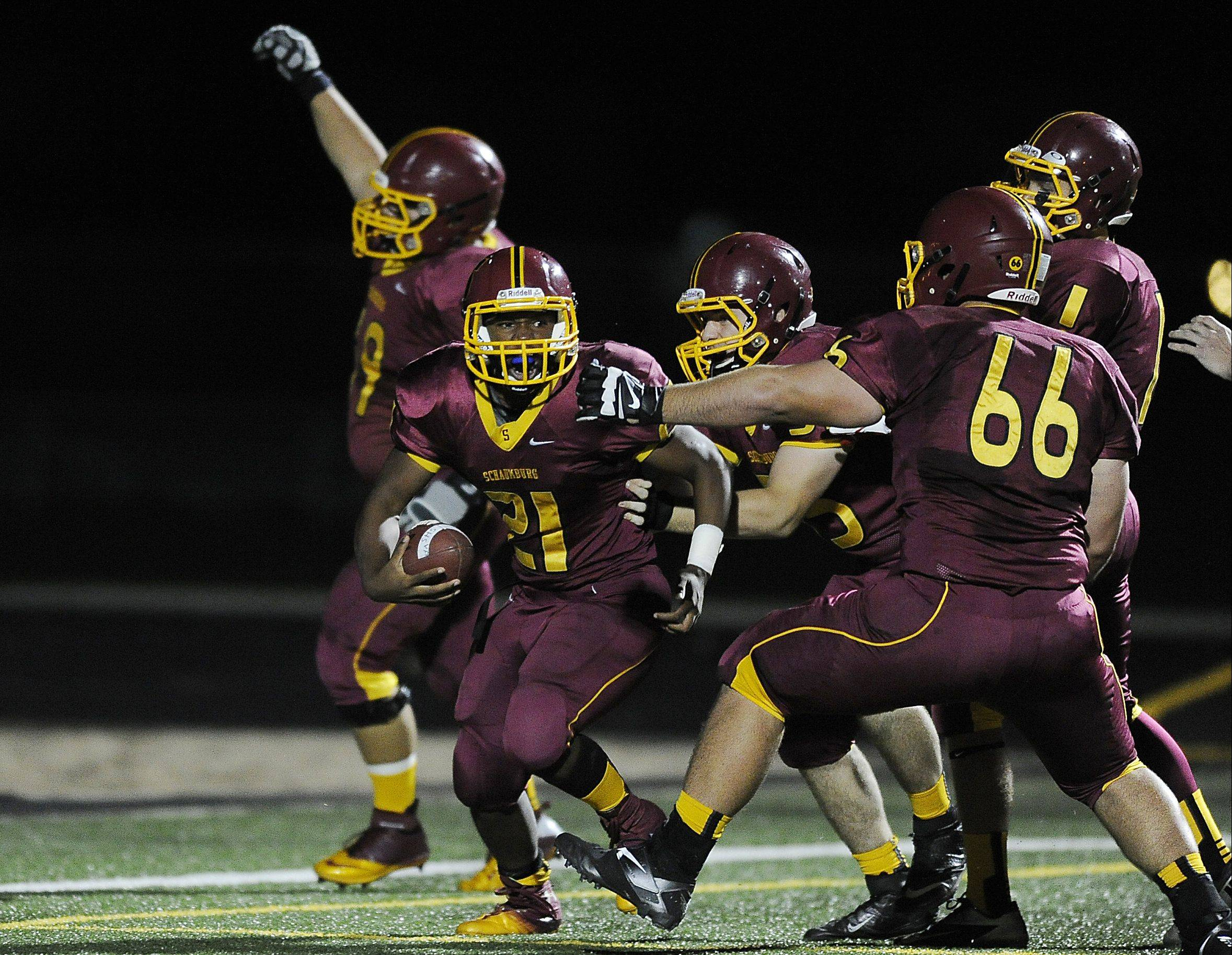 Schaumburg's Justice Macneal-Young celebrates his first quarter touchdown against Barrington with his teammates on Friday at Schaumburg.
