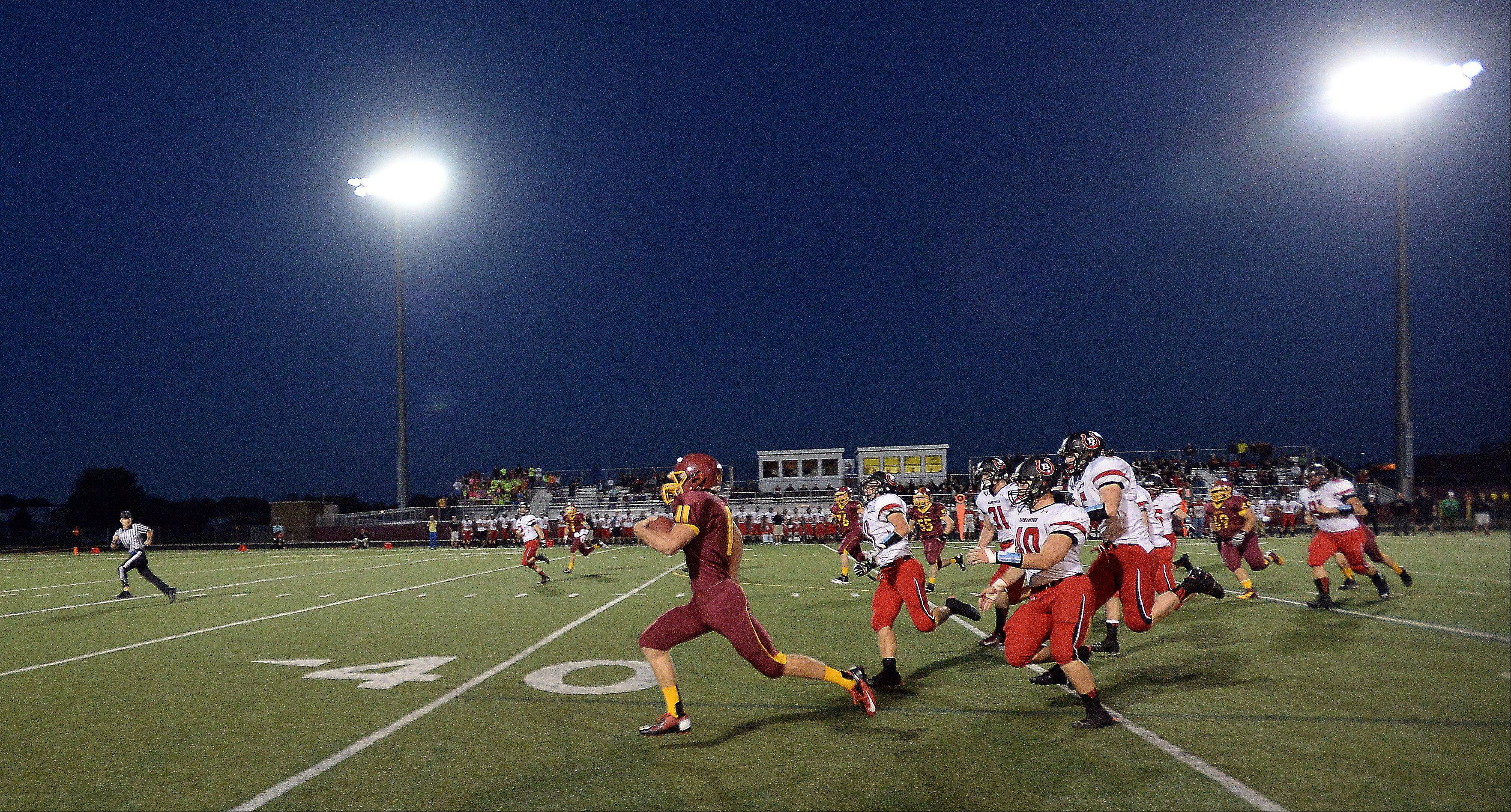 Schaumburg's Luke Gruszka runs 62 yards for a first-quarter touchdown against Barrington under the lights at Schaumburg on Friday.