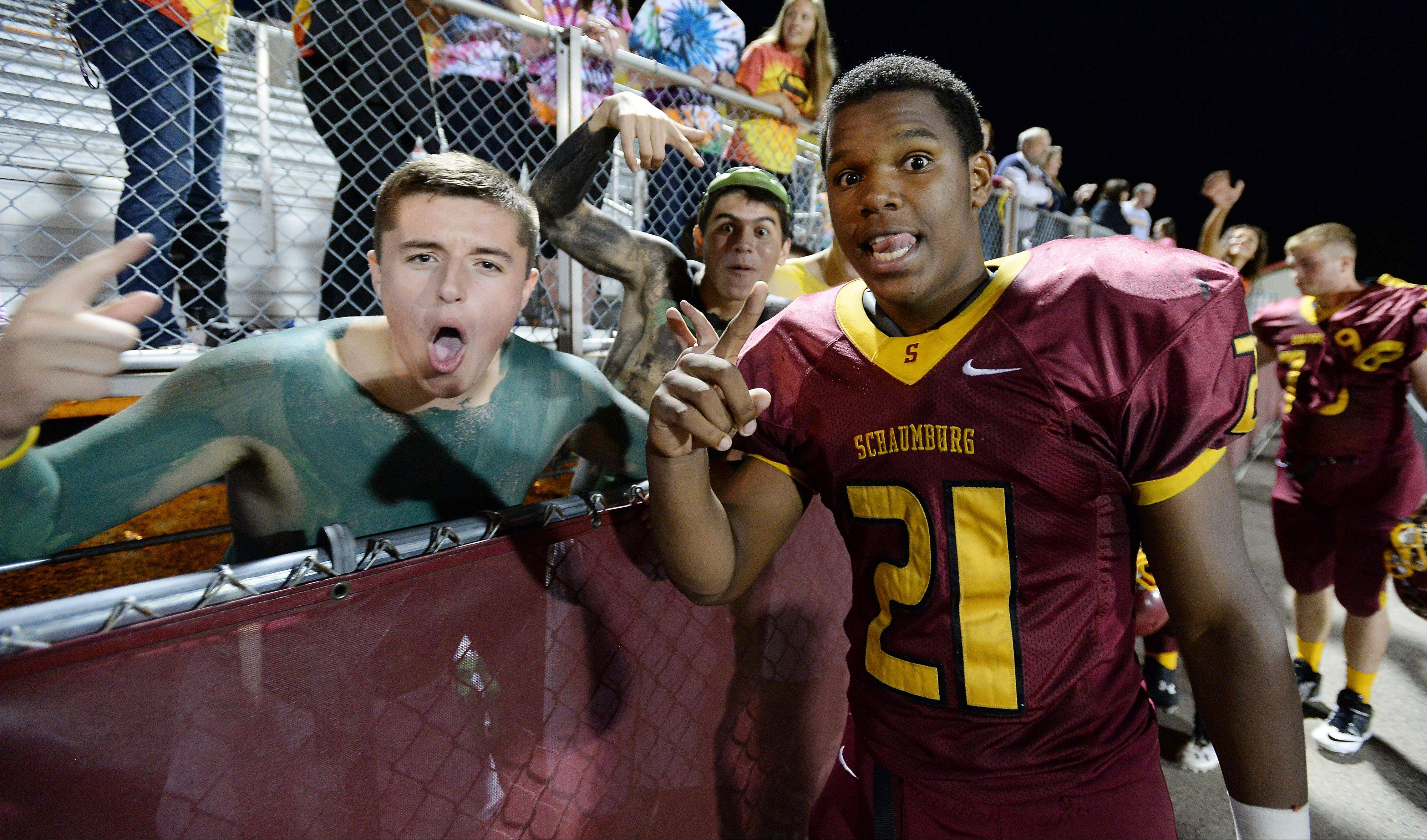 Schaumburg's Justice Macneal-Young celebrates with the fans after the Saxons topped Barrington 33-21 in matchup of unbeaten teams. Young finish with 3 touchdowns.
