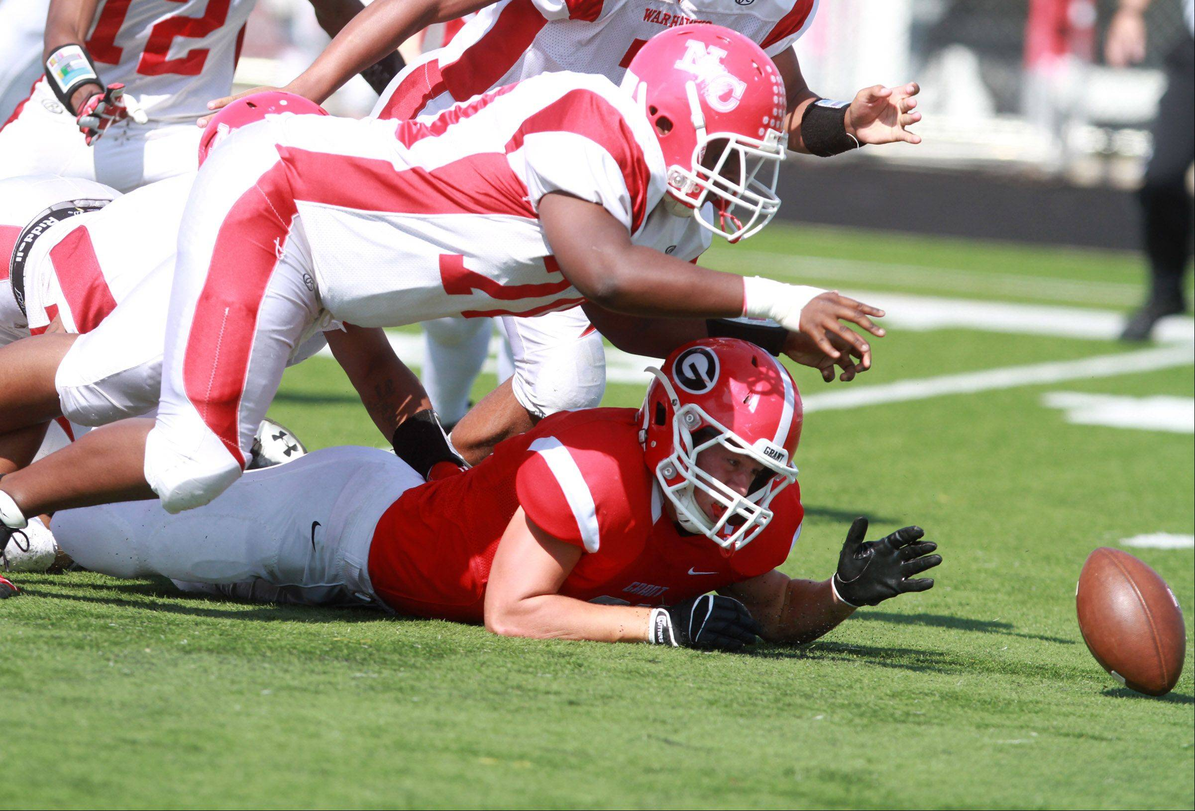 Grant running back Robert Dush, bottom, fumbles the football. It was recovered by North Chicago defender Darryl Coburn, above, at Grant on Saturday.