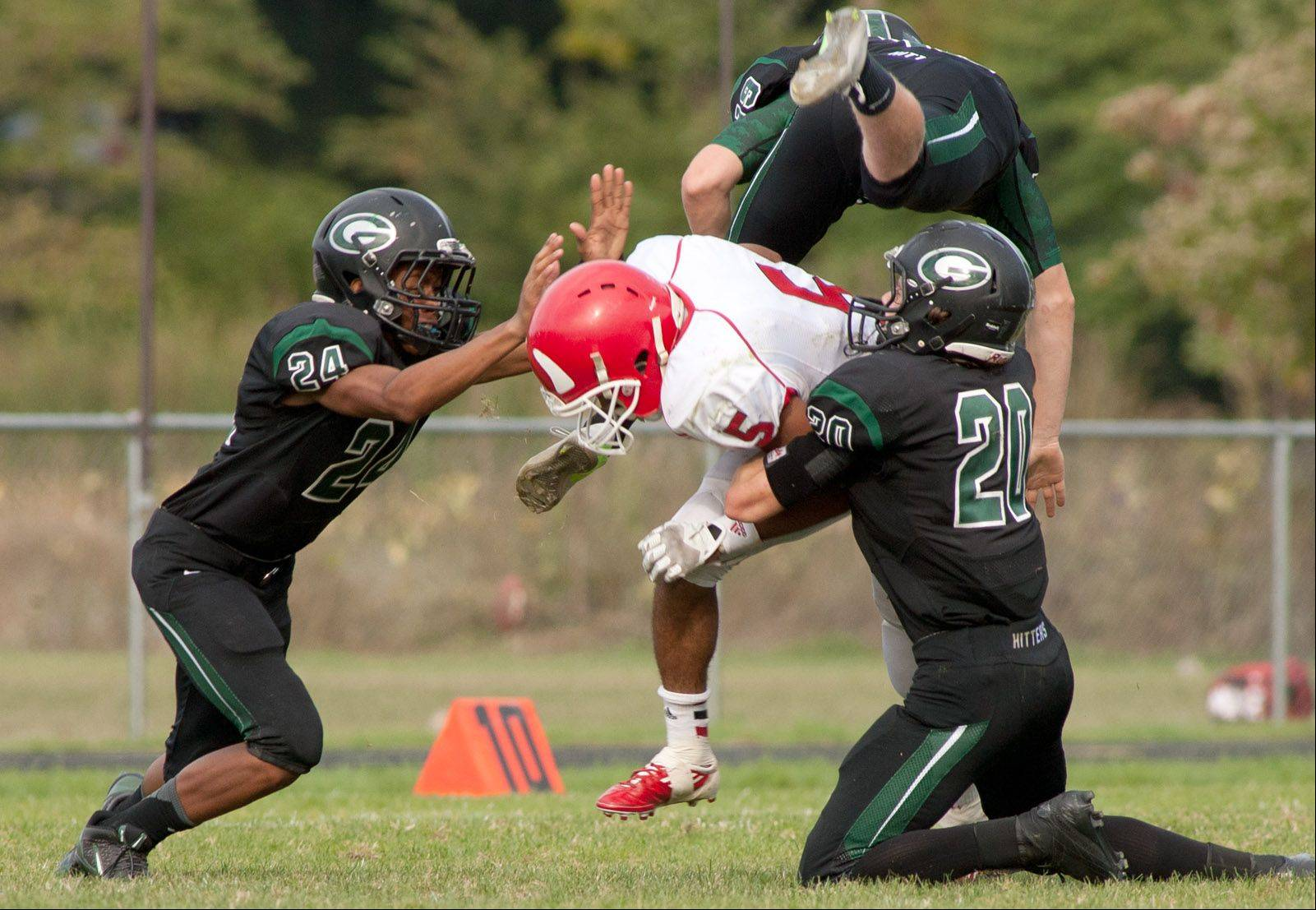 Hinsdale Central's Juwan Edmund, center, is tackled by Glenbard West's Ryan Thomas, left, and Jason Balogh, right,