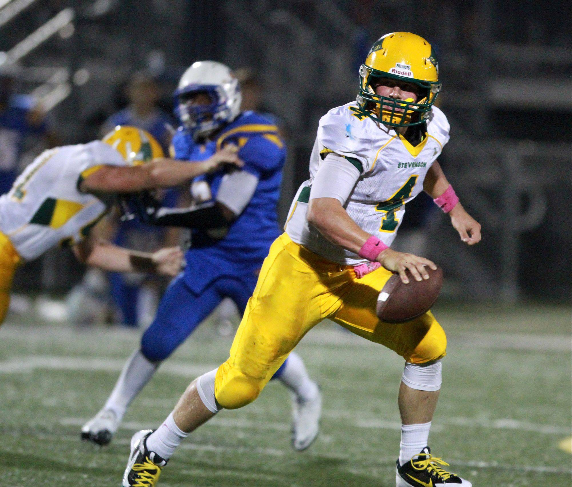 Stevenson quarterback Willie Bourbon scrambles with the ball against Warren on Friday.