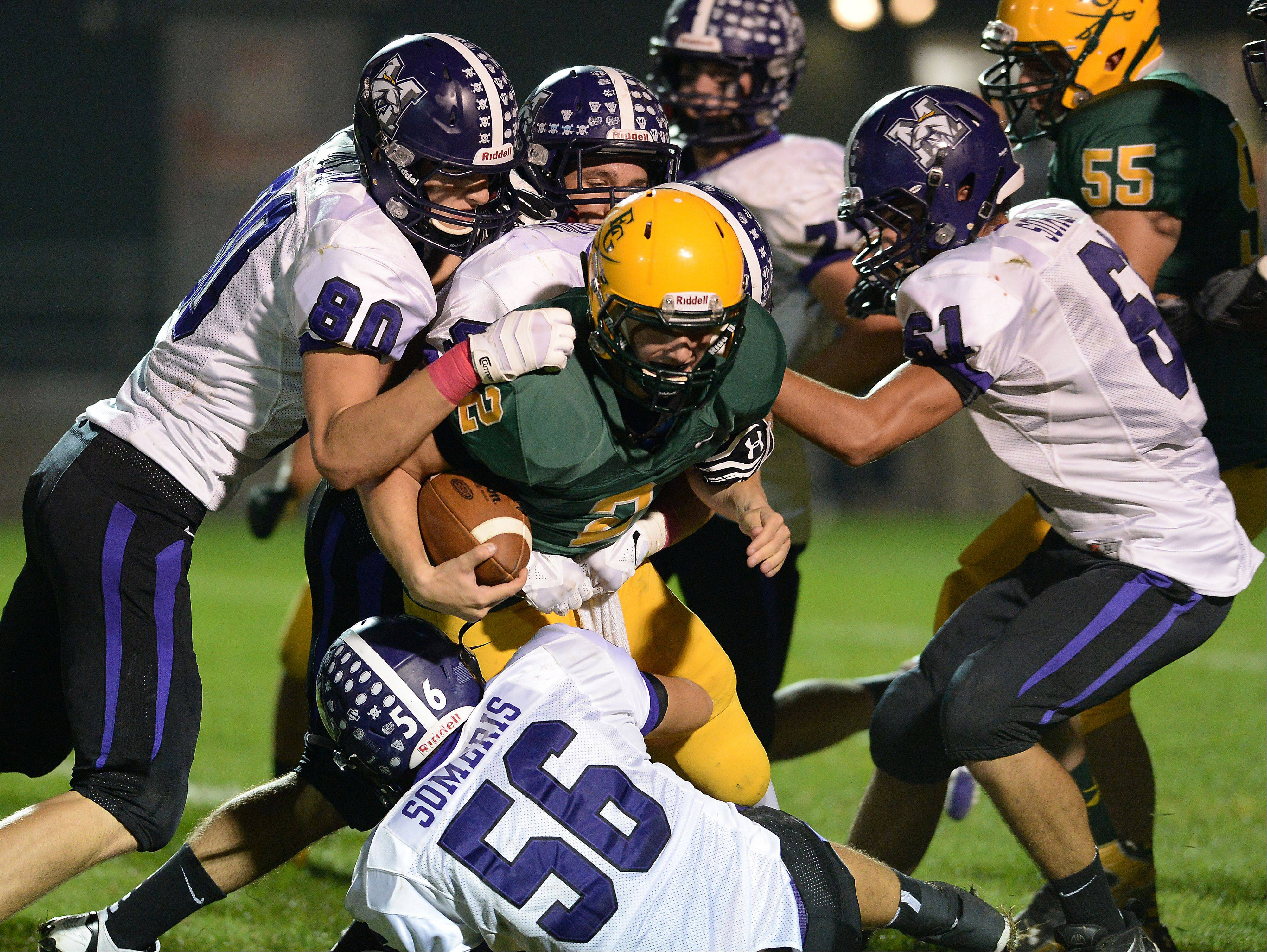 Elk Grove's Adam O'Malley succumbs to Rolling Meadows' Matt Dolan and a host of Mustangs defenders in the second quarter Friday at Elk Grove.