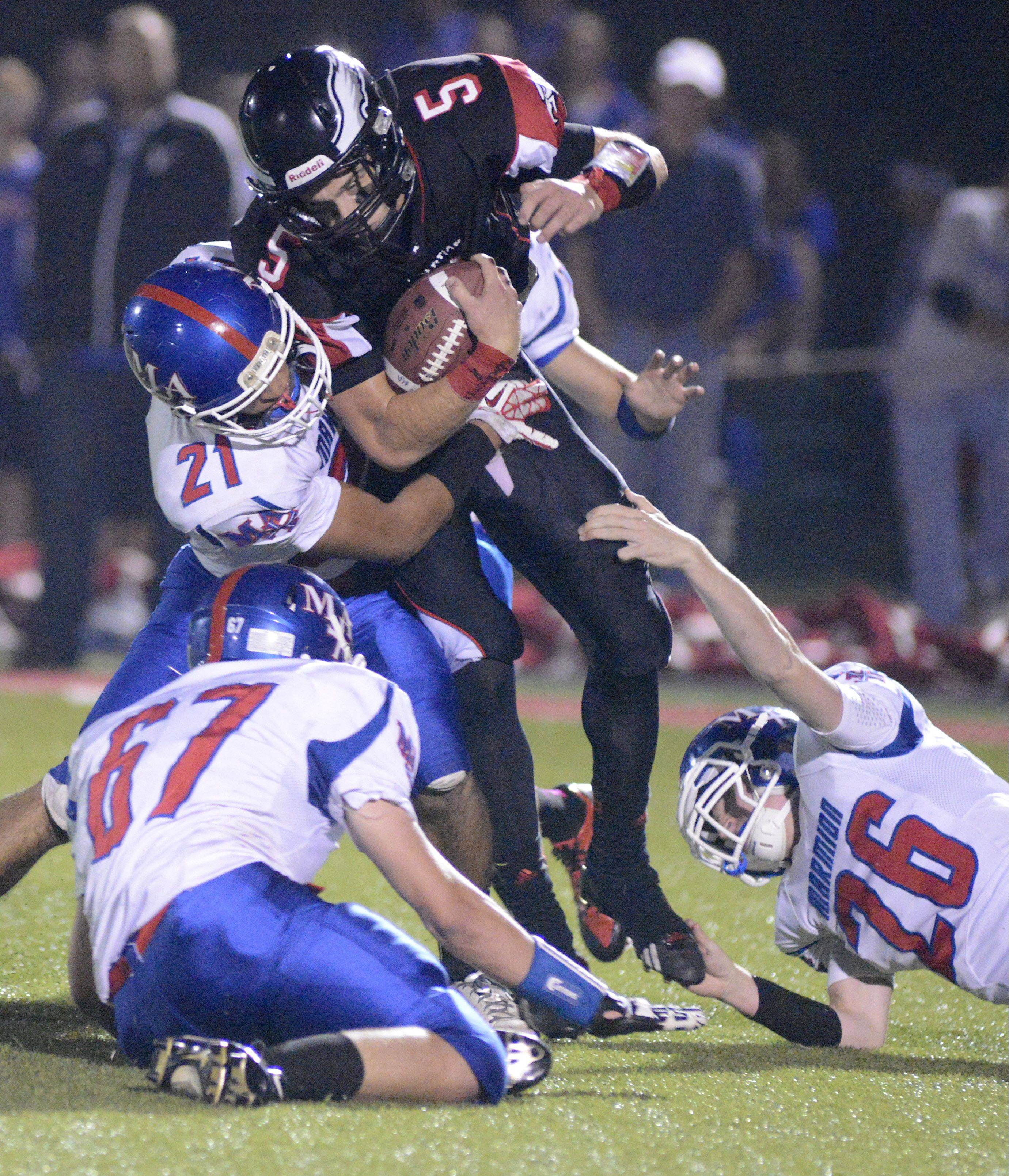 Marmion's defense made life tough on Aurora Christian Friday, with Enzo Olabi (21), Jimmy Rogers (67) and Matt Fredericks pictured here bringing down Noah Roberts.