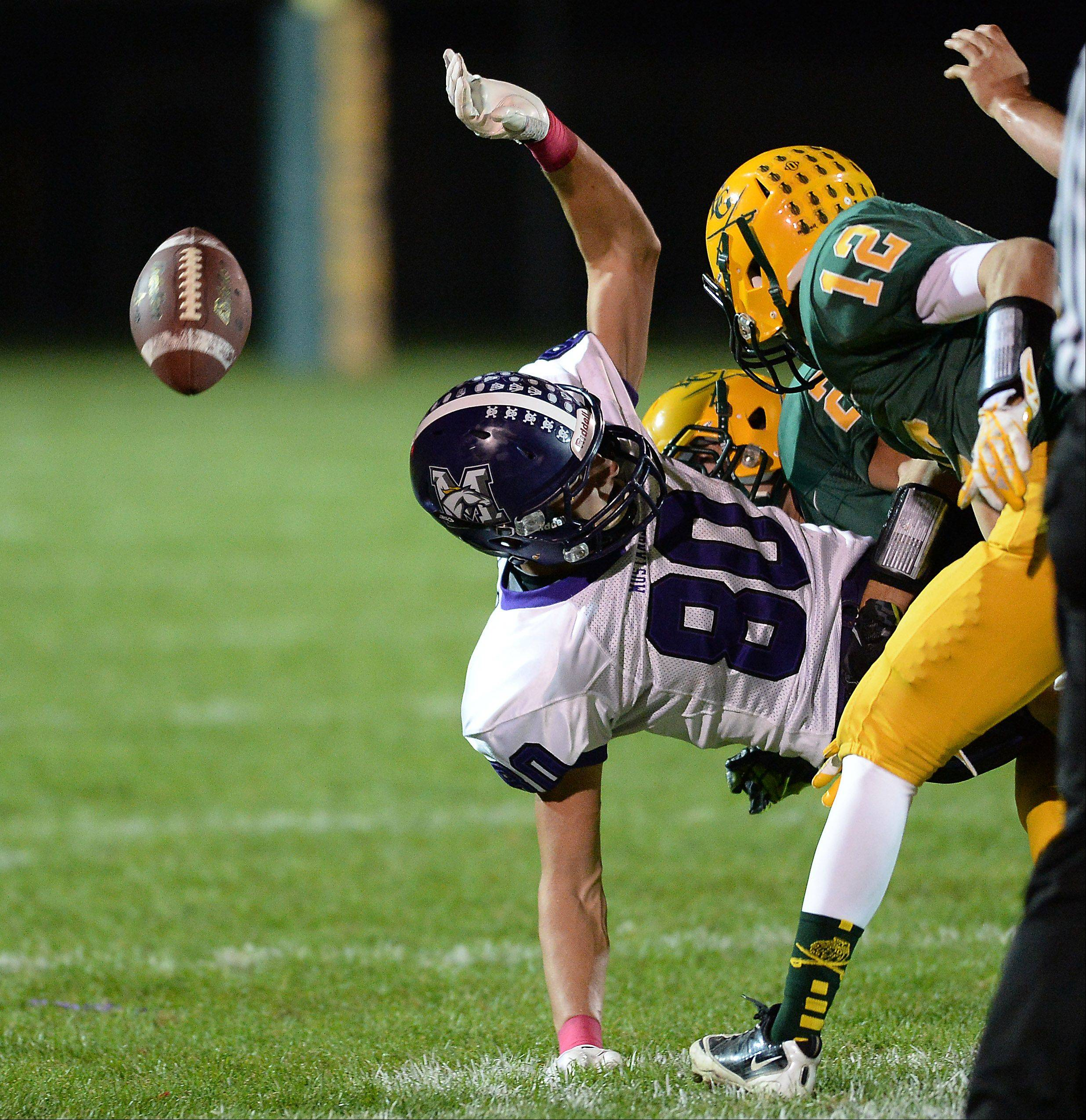Rolling Meadows' Matt Dolan gets hit and fumbles the football in the process.
