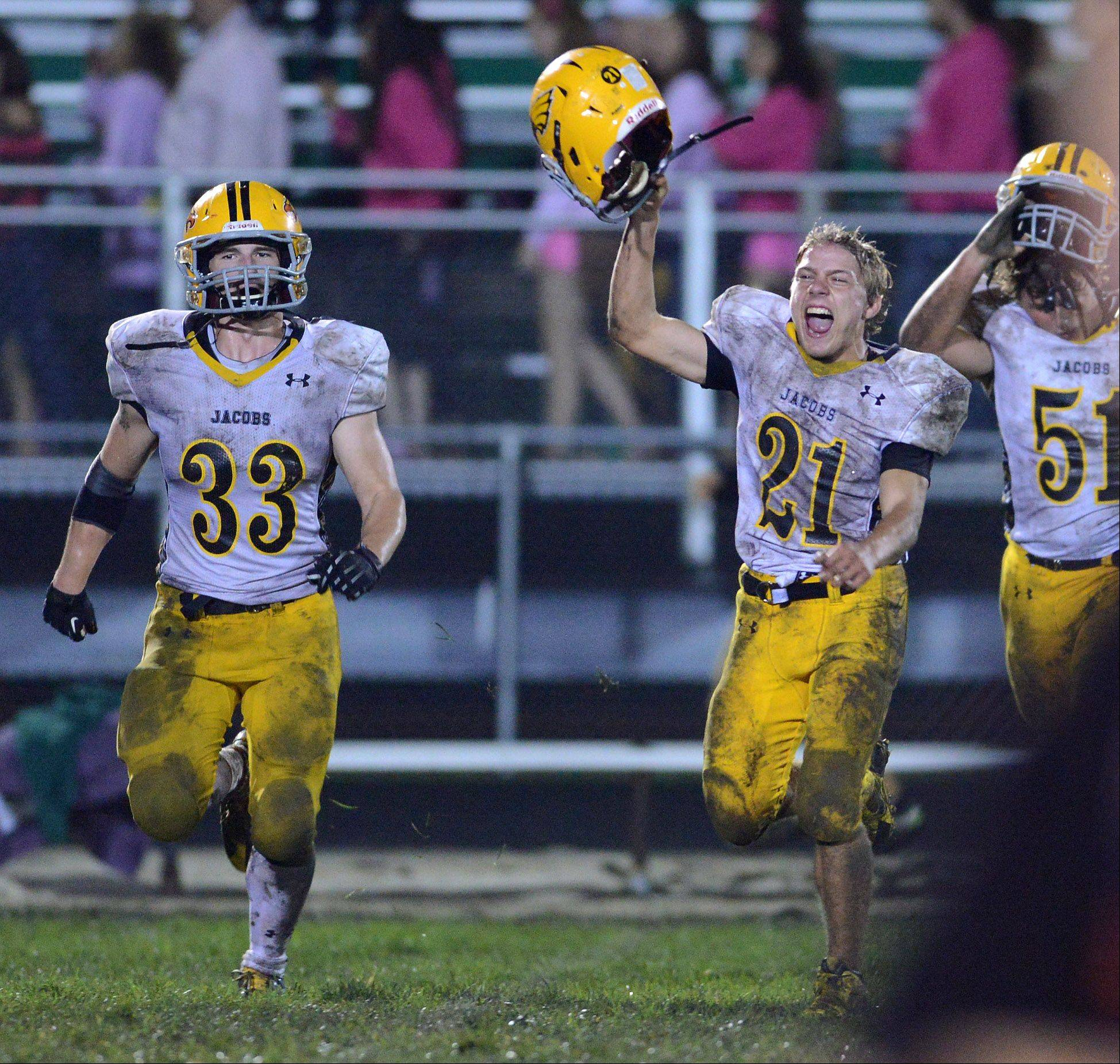 Jacobs' Greg McLeod , Cody Ferencz and Jeff Sidor run off the field following Friday's game in Crystal Lake.