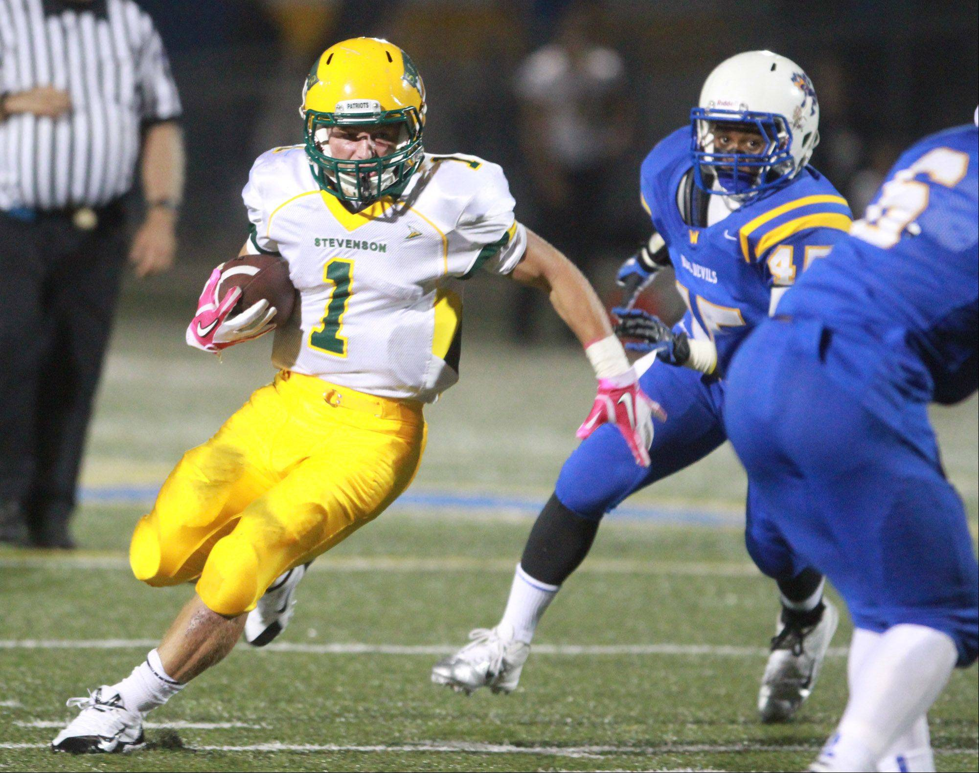 Stevenson running back Conor Okmin runs the ball against Warren.