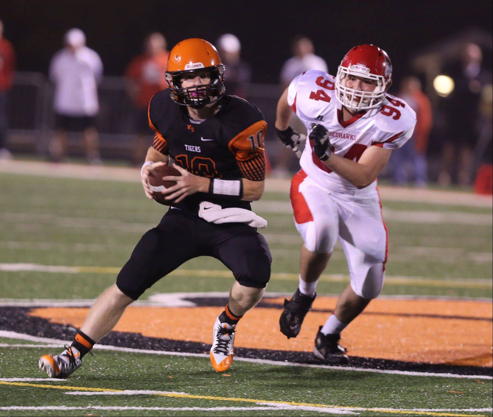 Wheaton Warrenville South quarterback Ryan Graham eludes Naperville Central's Louie Giovannetti .