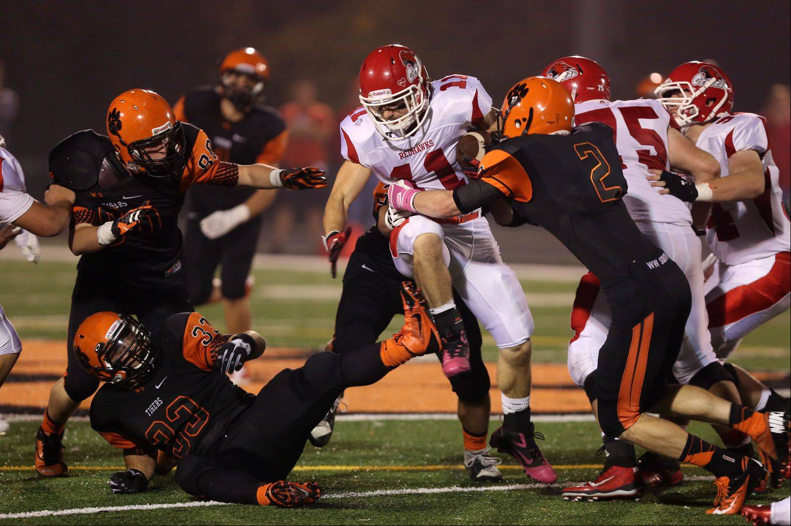 Naperville Central's Ben Andreas breaks through several Wheaton Warrenville defenders before being tackled by Matthew Brocious.