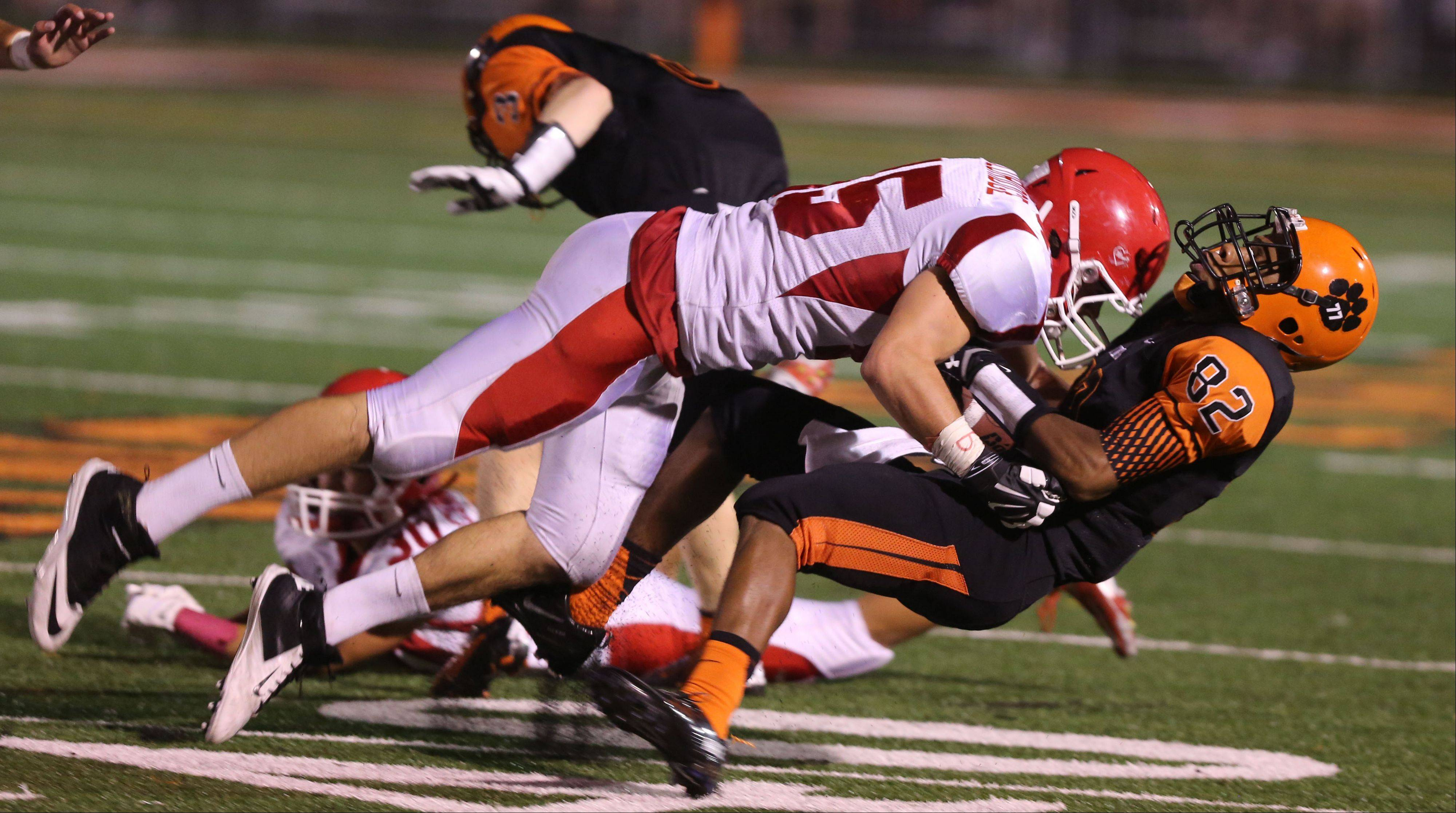 Wheaton Warrenville South's Keishawn Watson is leveled by a Naperville Central defender.