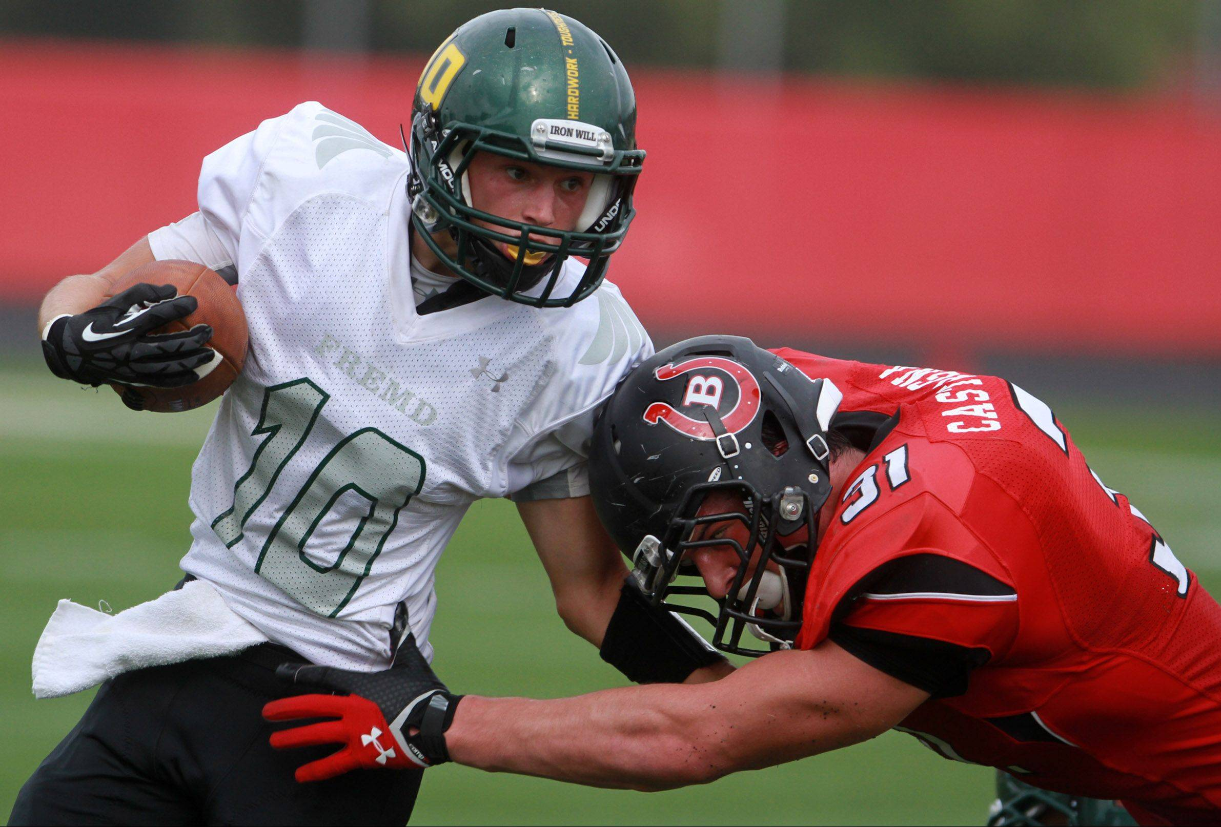 Fremd receiver Anthony Halvorsen is pulled down by Barrington defender Colin Castagna at Barrington on Saturday.