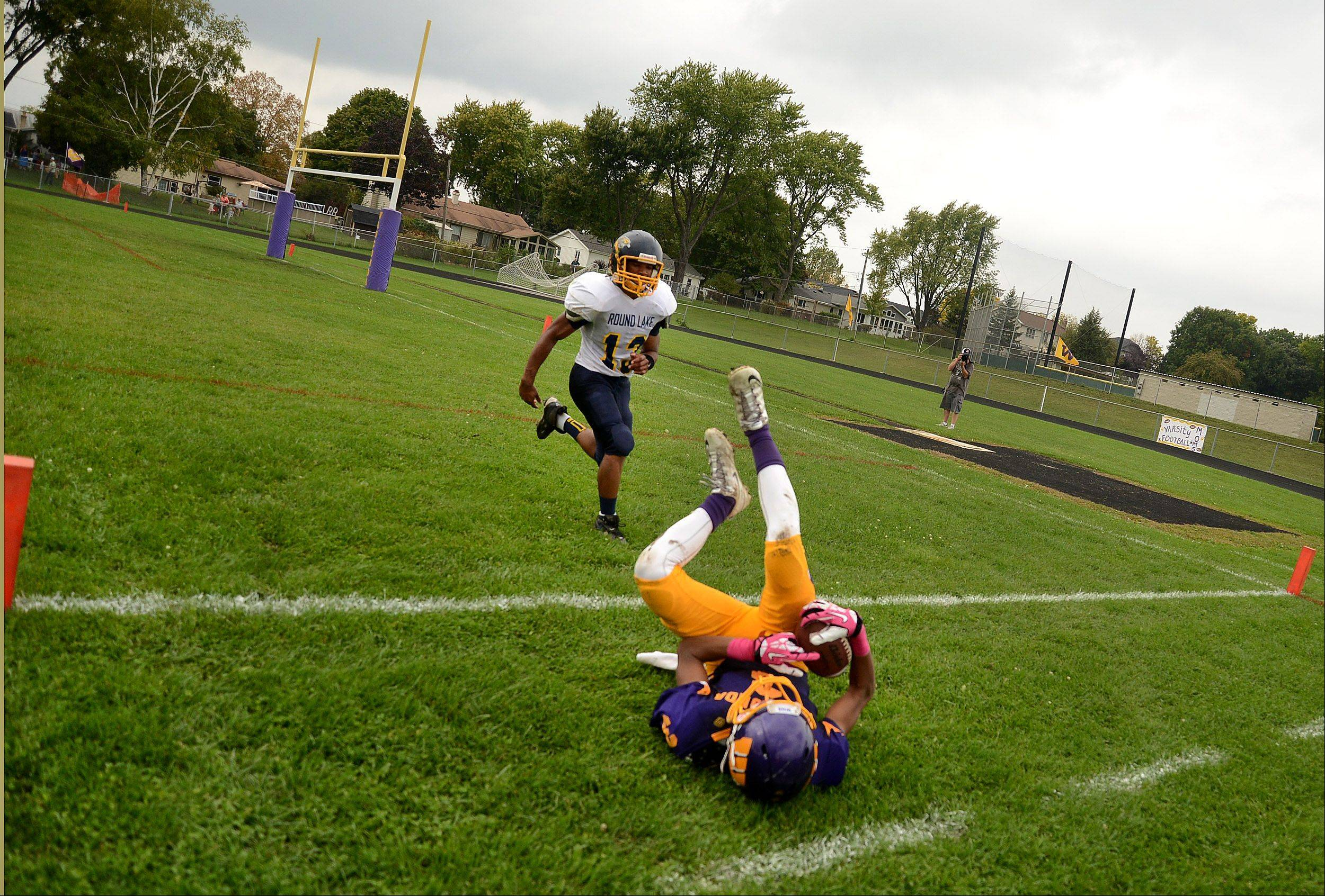 Wauconda's Josh Anderson keeps control of the ball as he rolls through the end zone for a touchdown against Round Lake.