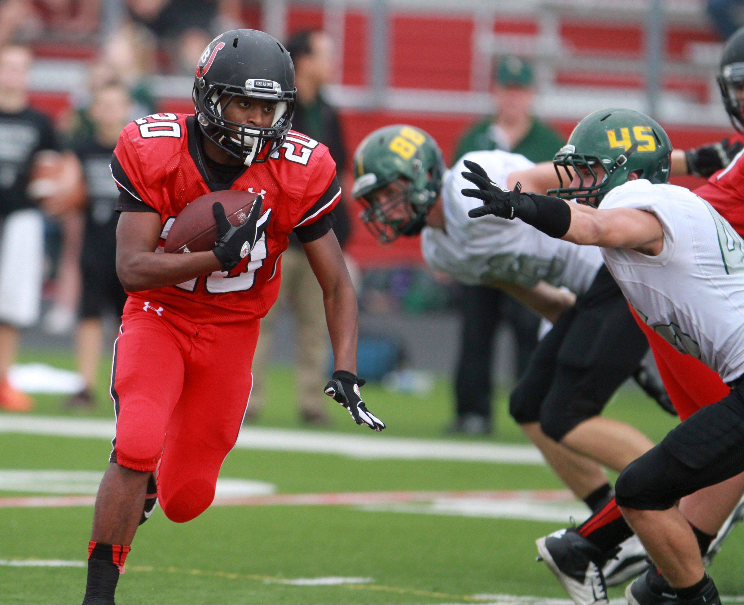 Barrington wide-receiver Jeff Gill runs around two Fremd defenders at Barrington on Saturday,October 5.