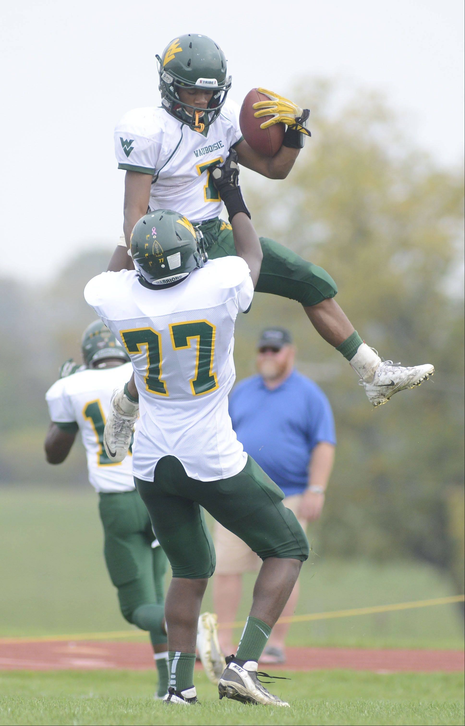 Waubonsie Valley's Tony Durns is hoisted into the air by teammate Jon Harris after scoring a touchdown in the first quarter on Saturday, October 5.