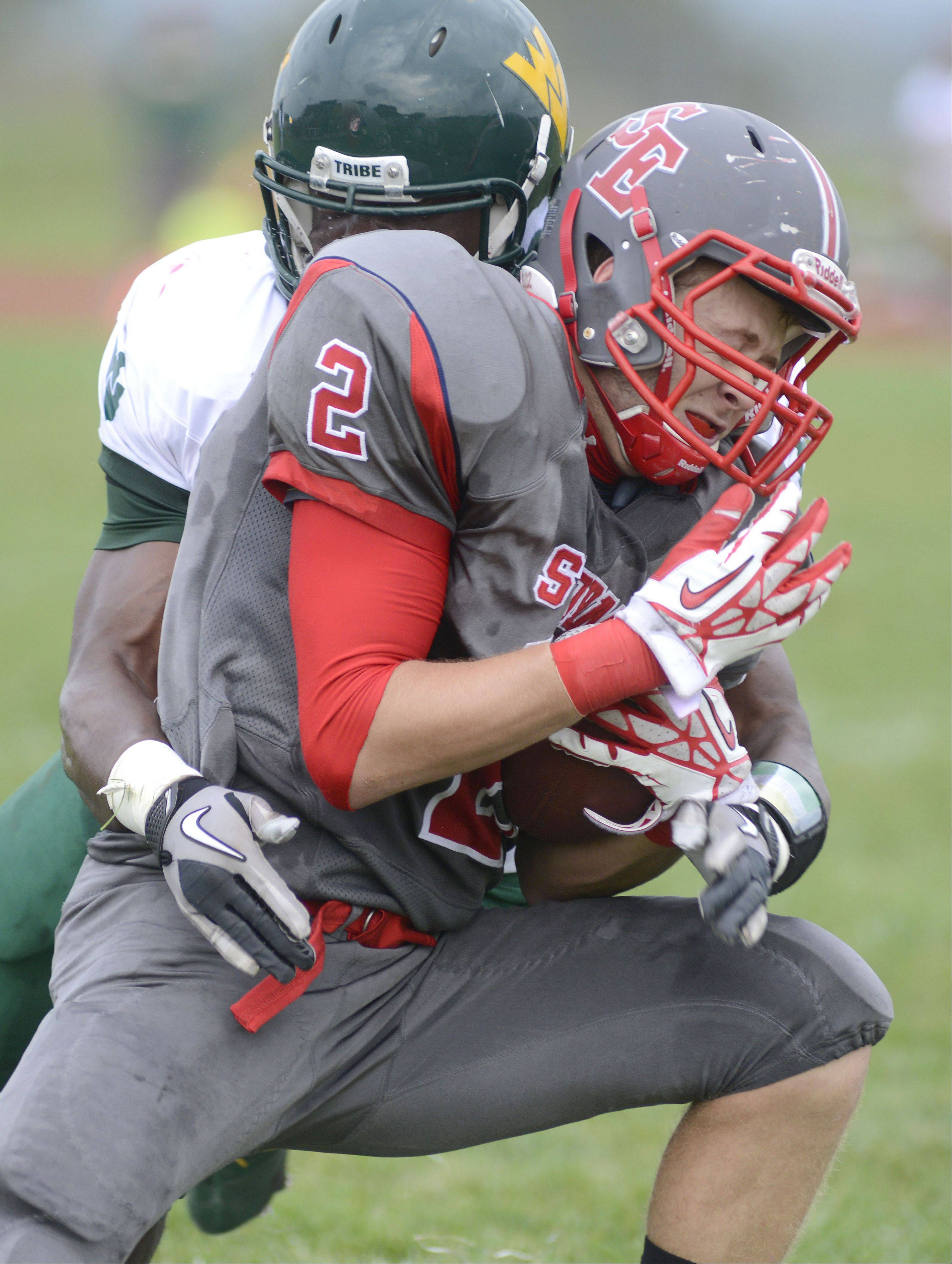 South Elgin's Andrew Kamienski is tackled hard by Waubonsie Valley's DeMario Webb in the first quarter on Saturday, October 5.