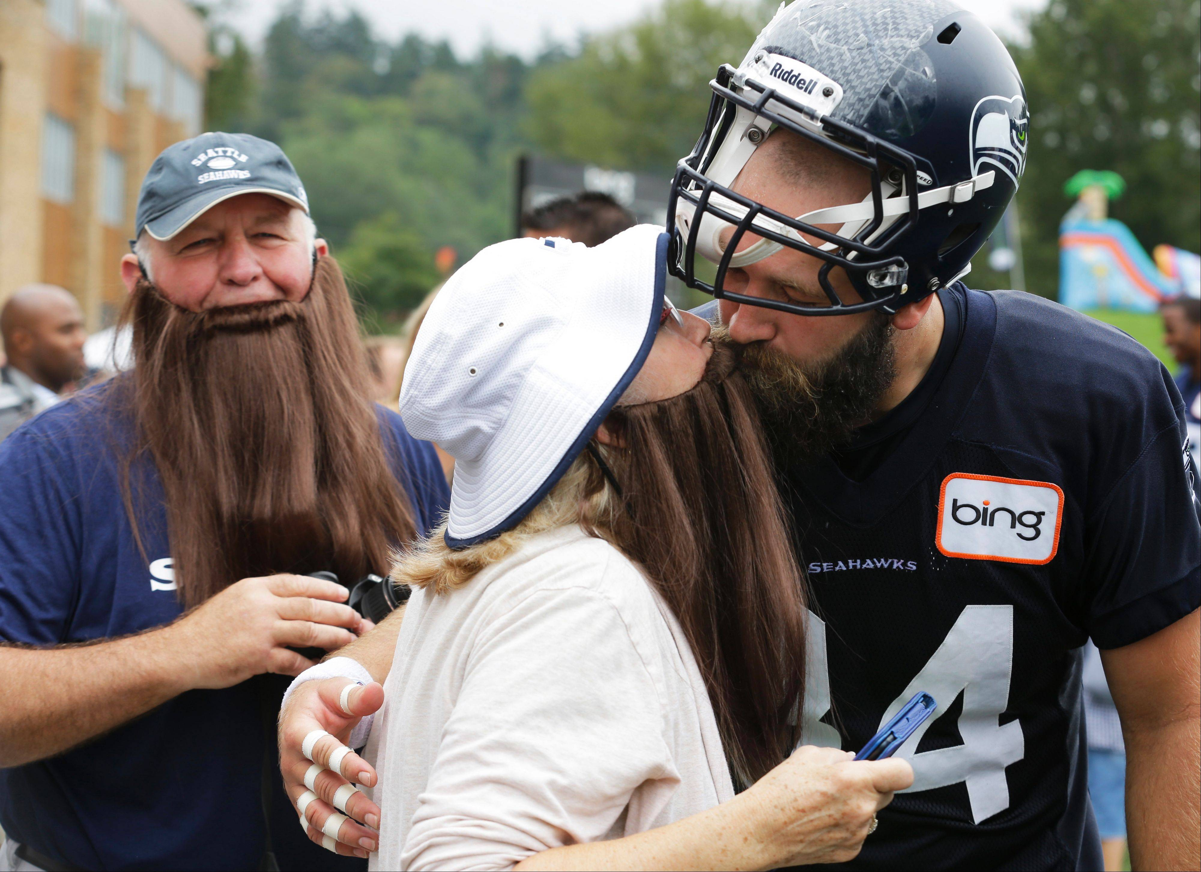 Seattle Seahawks tight end Sean McGrath kisses his mother, Nita McGrath, as his father Pat McGrath watches. The McGraths wore fake beards in tribute to their son, who was in training camp with the team. Sean was later cut and signed by the Kansas City Chiefs.