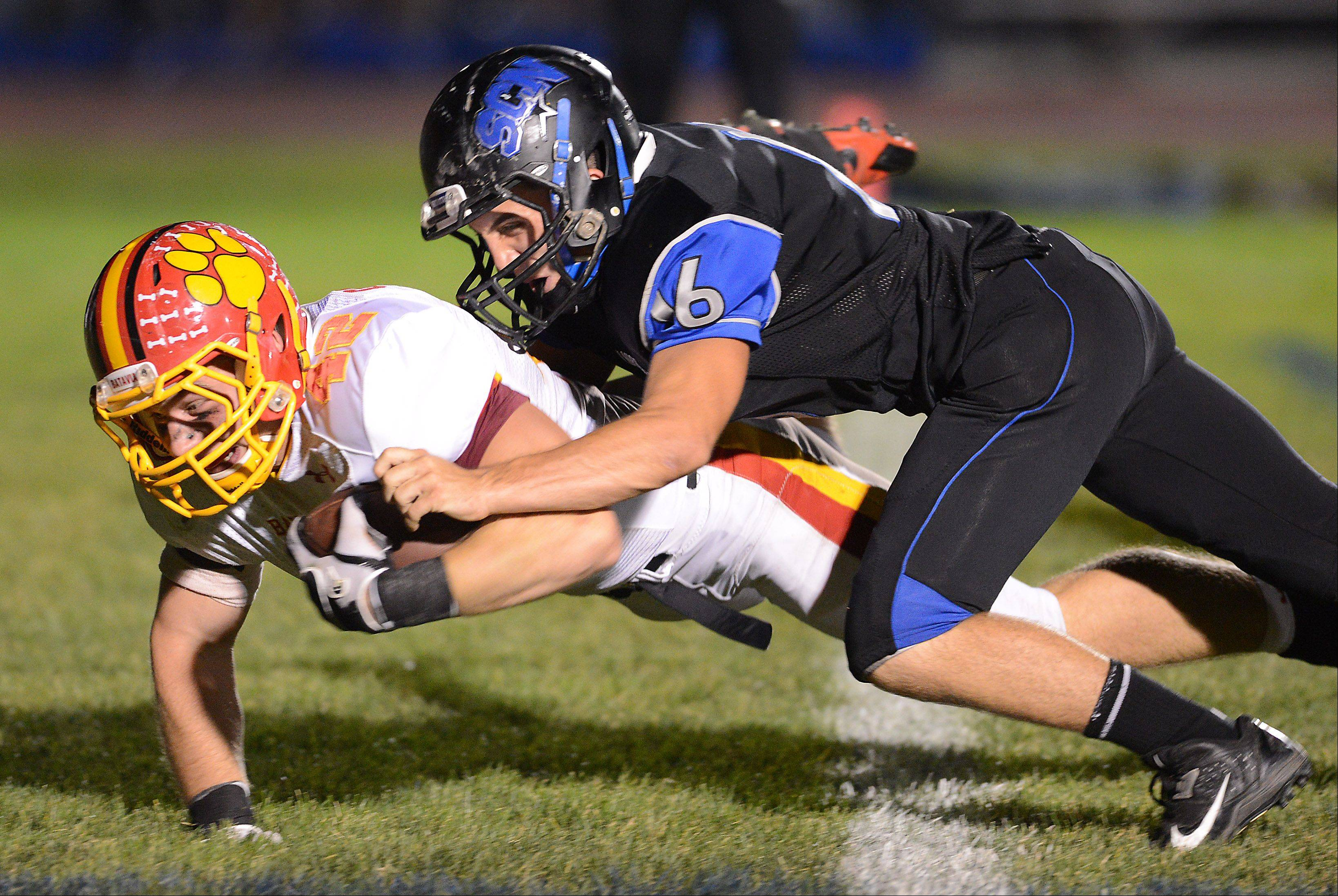 Batavia's Kevin Green (42) dives across the goalline under pressure from St Charles North's Tyler Bell for a touchdown to put the Bulldogs up 19-0 against St. Charles North Friday's game in St. Charles.