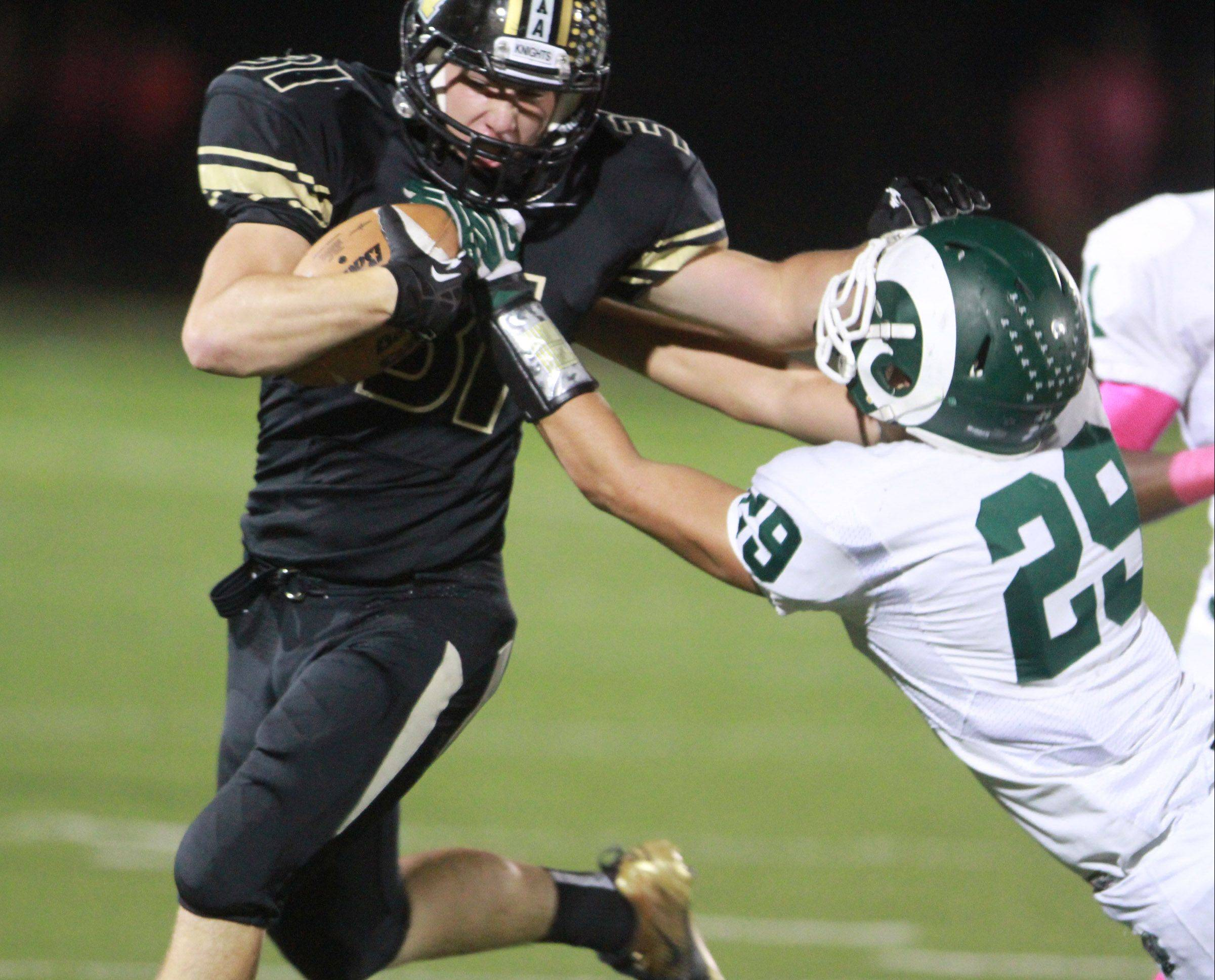 Grayslake North running back Brad Baker is pulled down by Grayslake Central linebacker Jaron Armiger at Grayslake North on Friday.