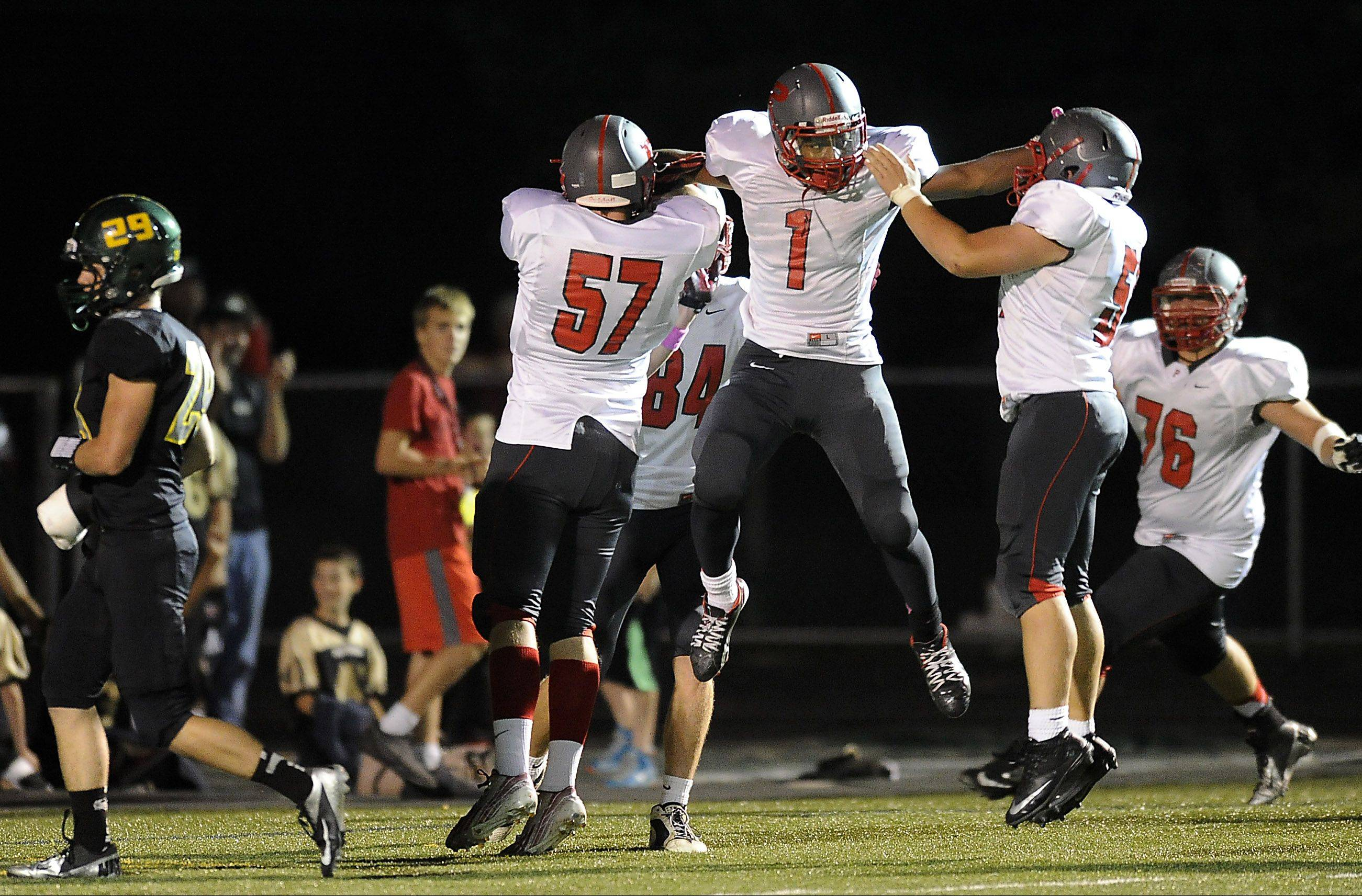Palatine's Chris Cornelius (middle) celebrates his second-quarter touchdown with teammates Jesus Cordova and Kevin Clark on Friday at Fremd.